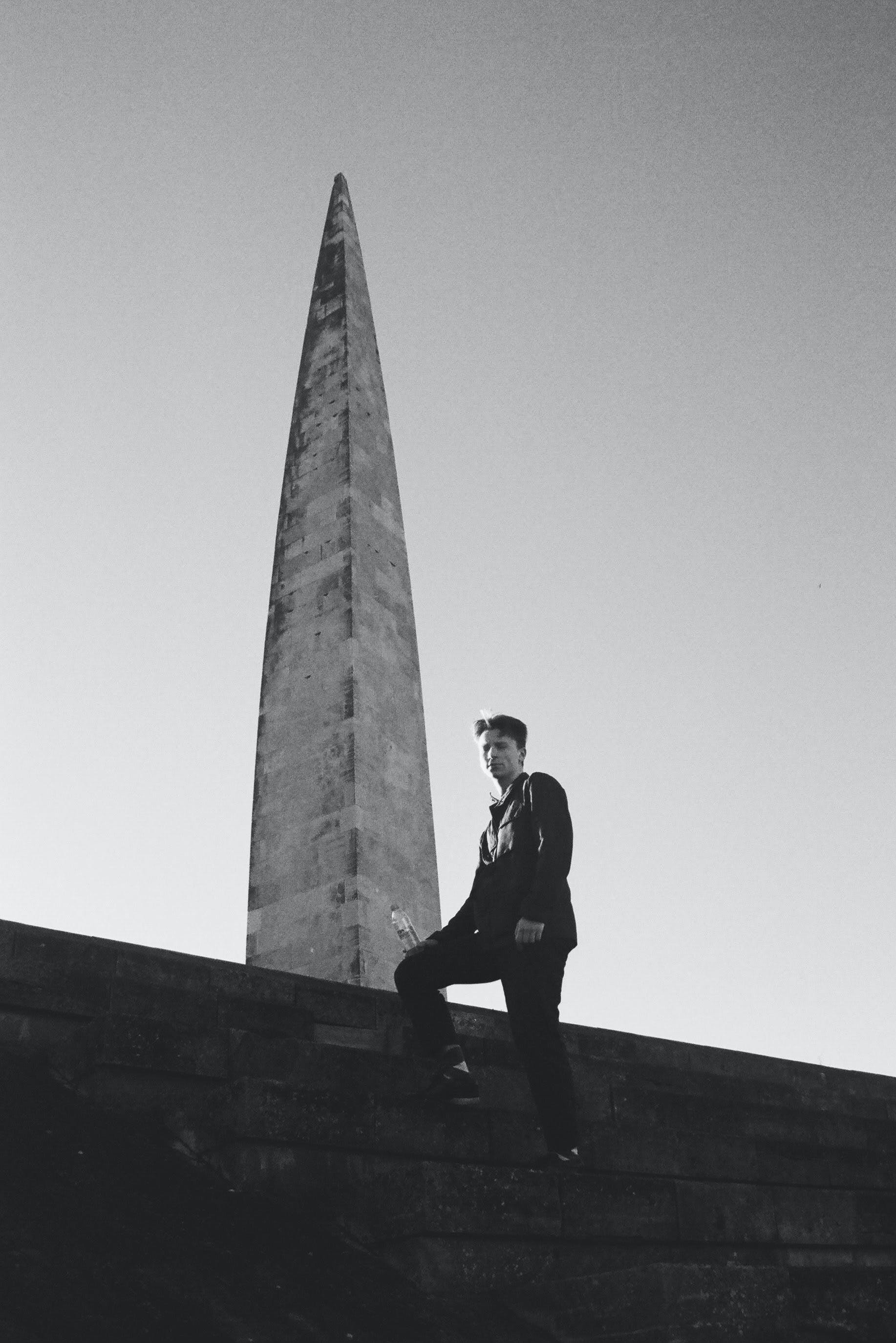 Grayscale Photo of Man Standing Beside Monument