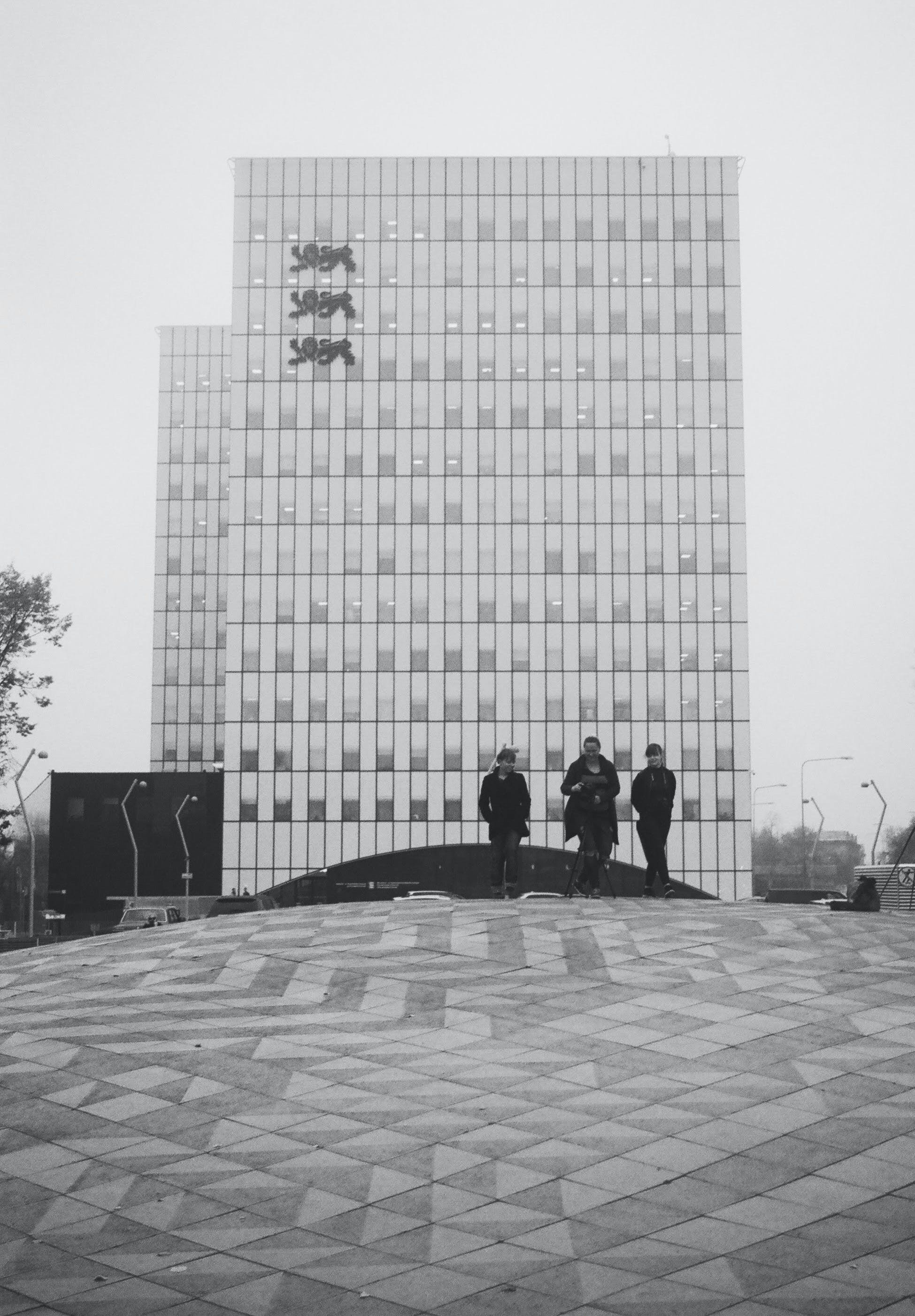 Grayscale Photo of Three People Near a Building