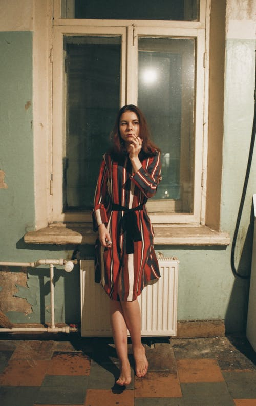 Woman Wearing Red, White, and Black Striped Long-sleeved Flare Dress Standing Beside Window Pane