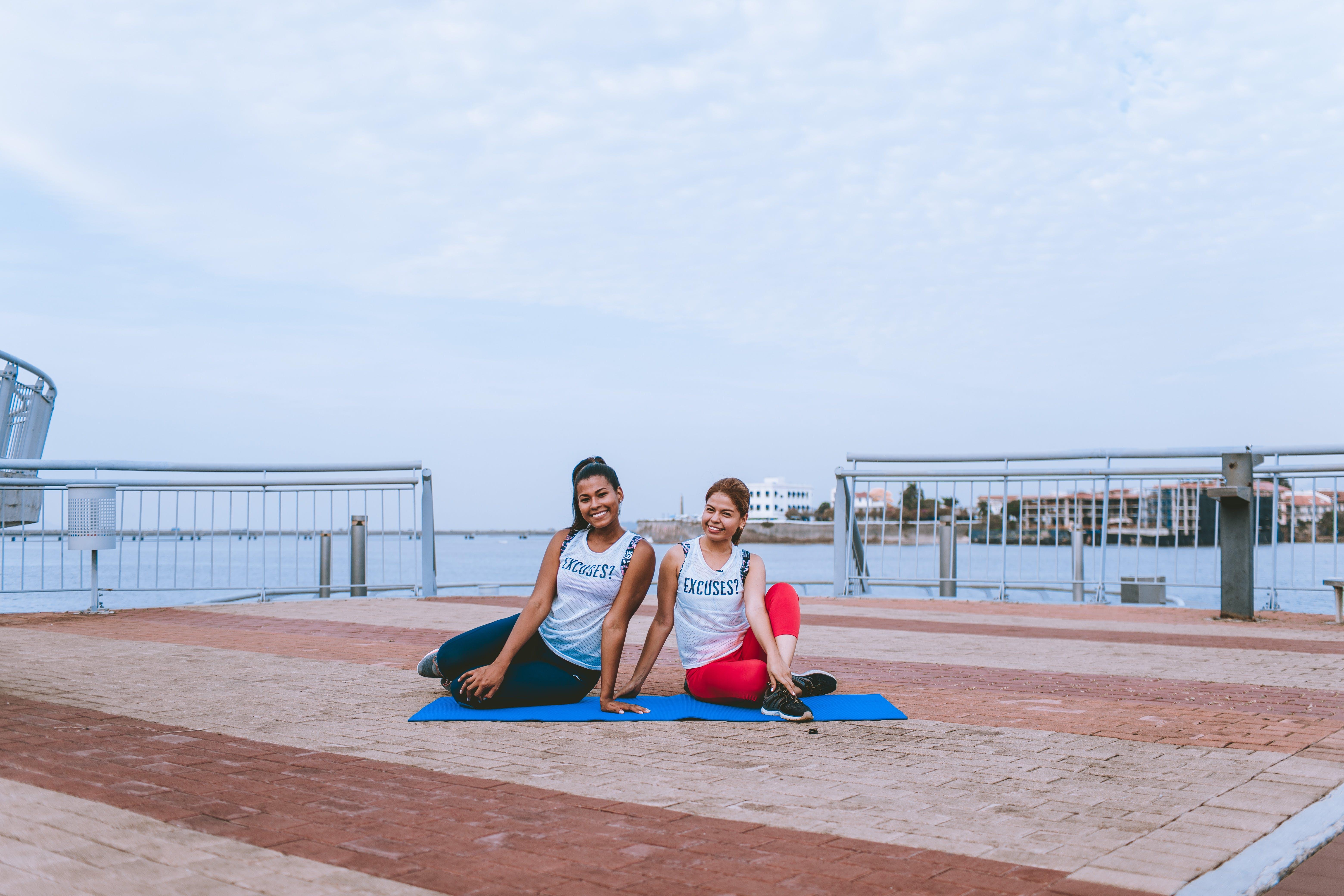 Two Women Sitting on Yoga Mat