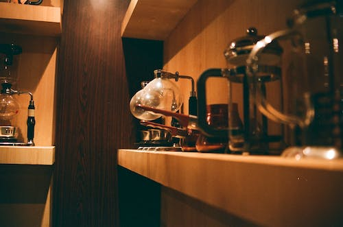 Selective Focus Photography of Coffee Pitchers on Shelf