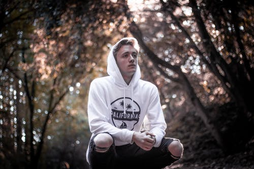 Man in white hoodie Squatting