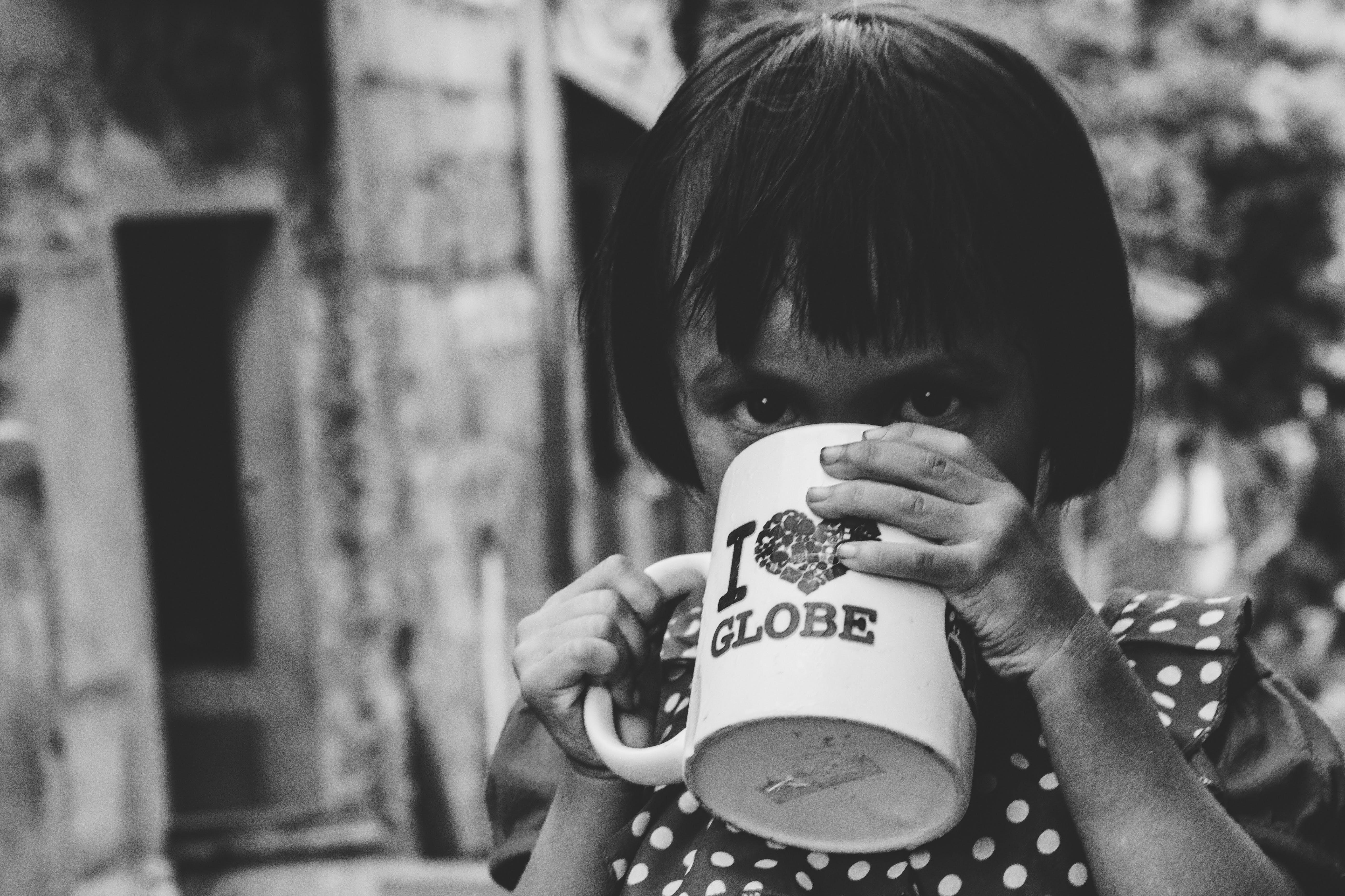Grayscale Photography of Girl Drinking Water on Mug