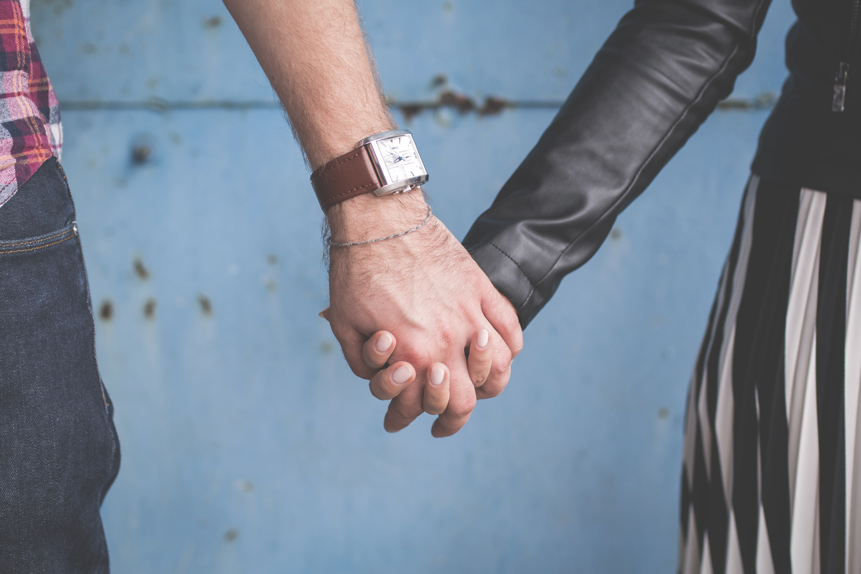 2 Person Holding Hands Besides Blue Painted Wall