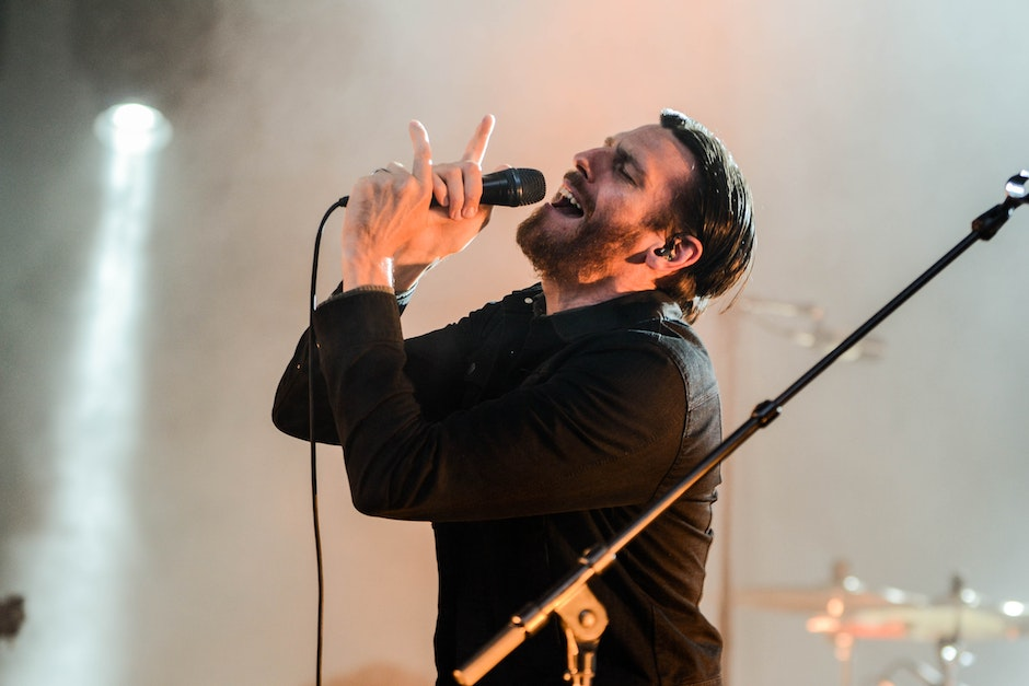 Man Wearing Black Collared Long Sleeve Shirt Holding Microphone