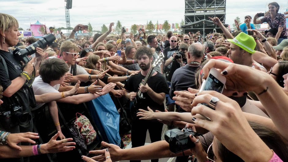 Man in Black Crew Neck T Shirt and Pants Playing Guitar Surrounded by Crowd
