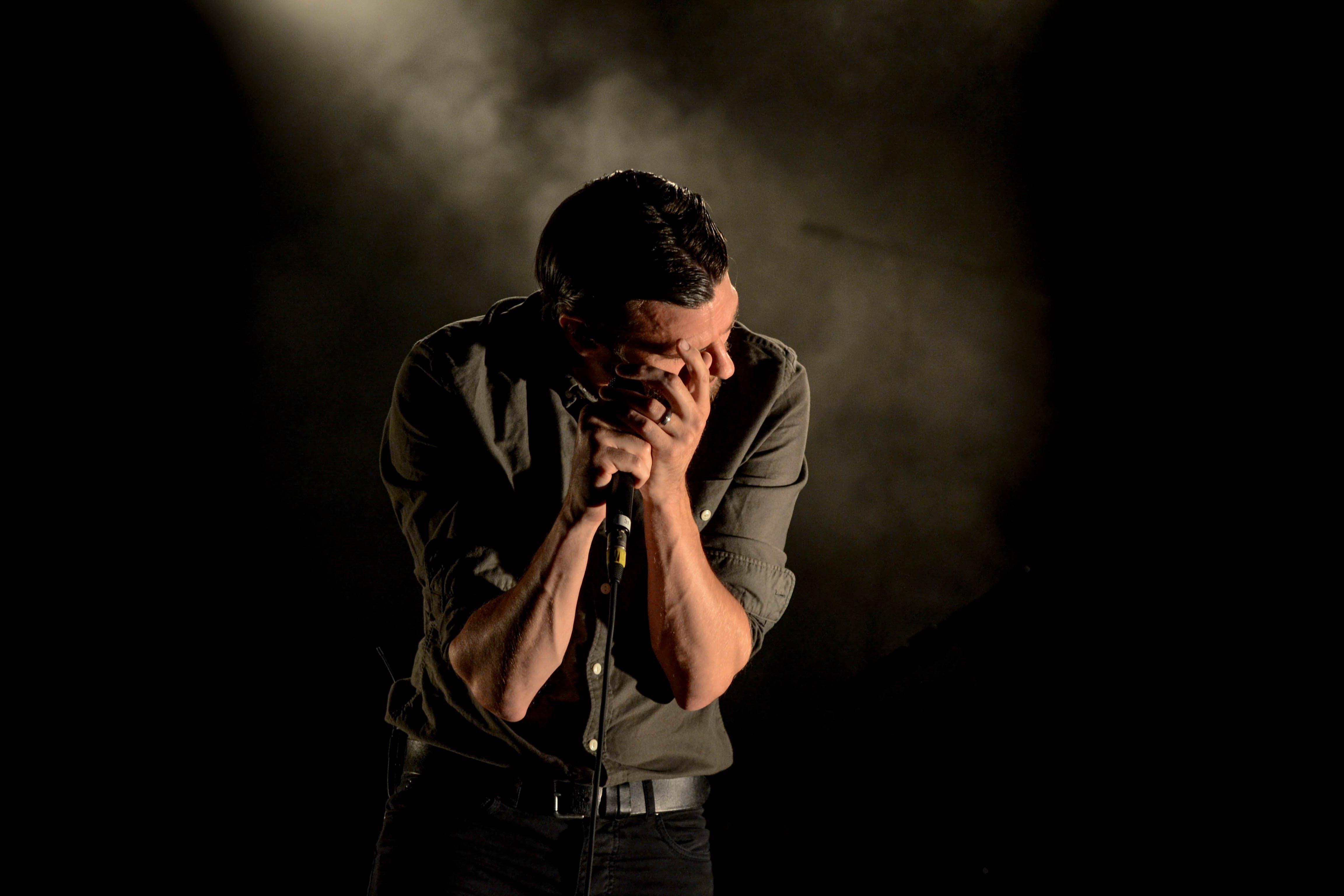 Man in Gray Dress Shirt Holding Mic in Dark Room