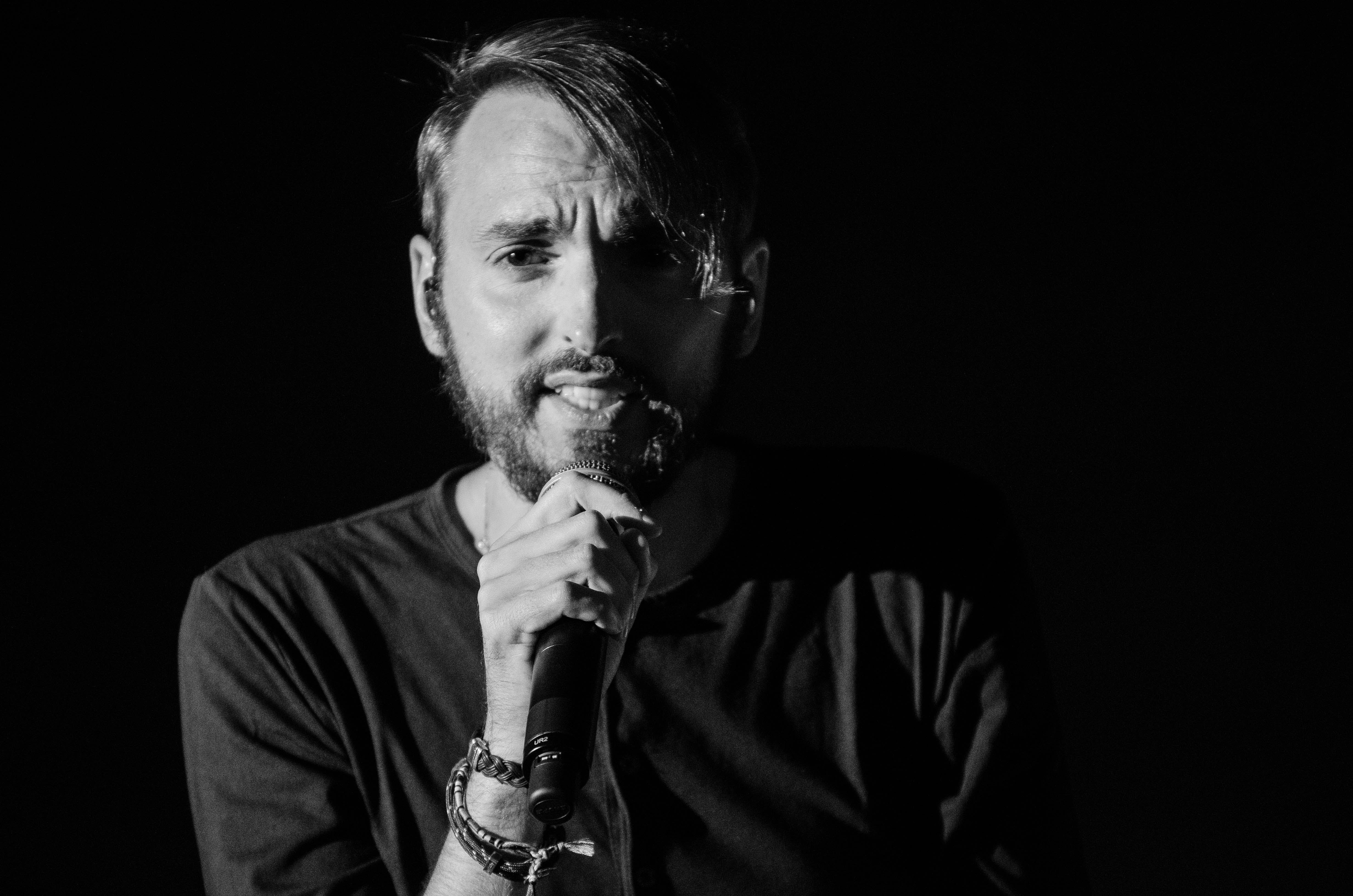 Grayscale Photo of Man Holding Microphone