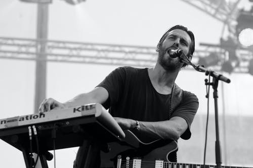 Grayscale Photo of Man Playing Electric Keyboard
