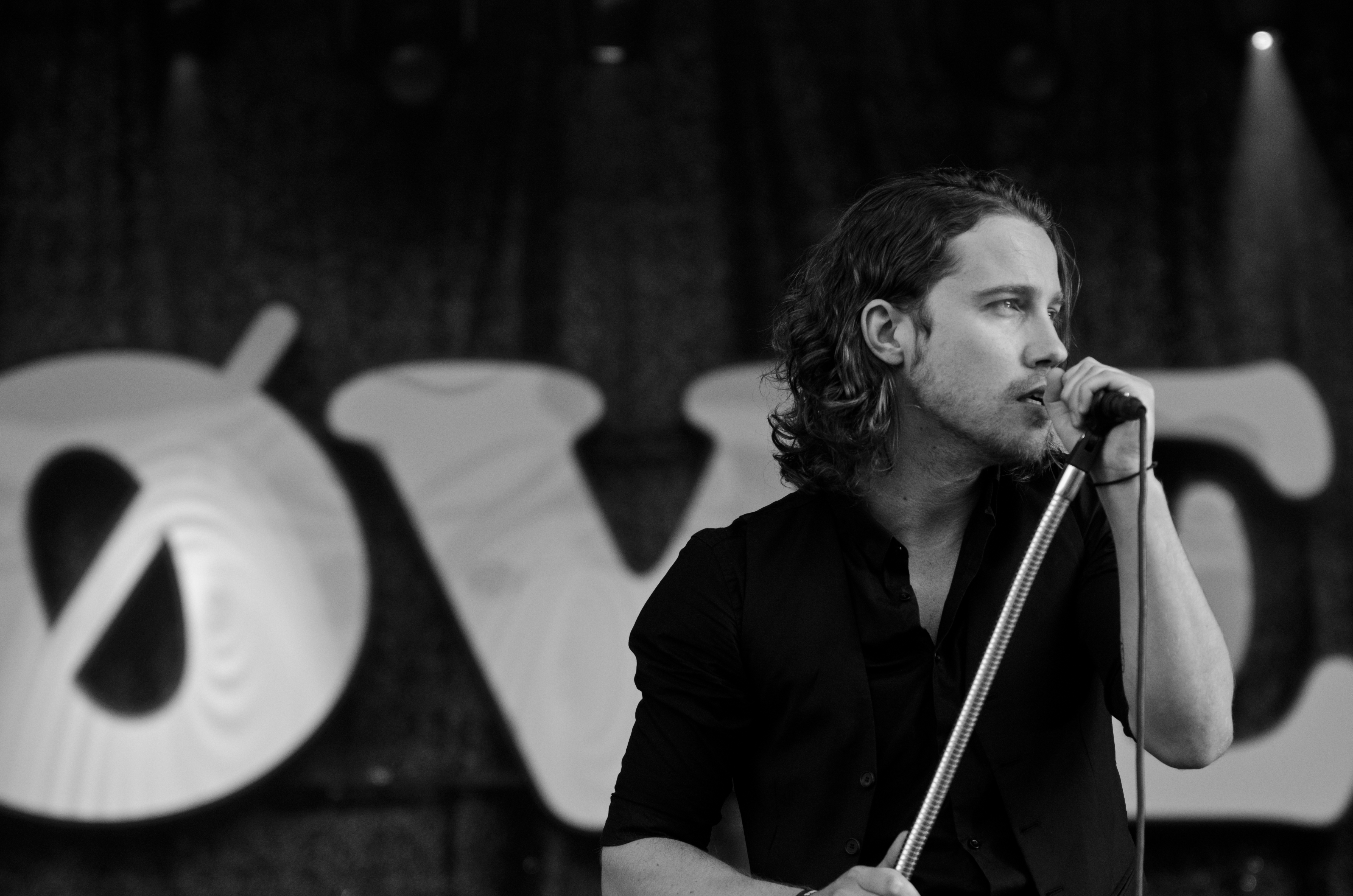 Grayscale Photography of Man Wearing Dress Shirt While Holding Microphone