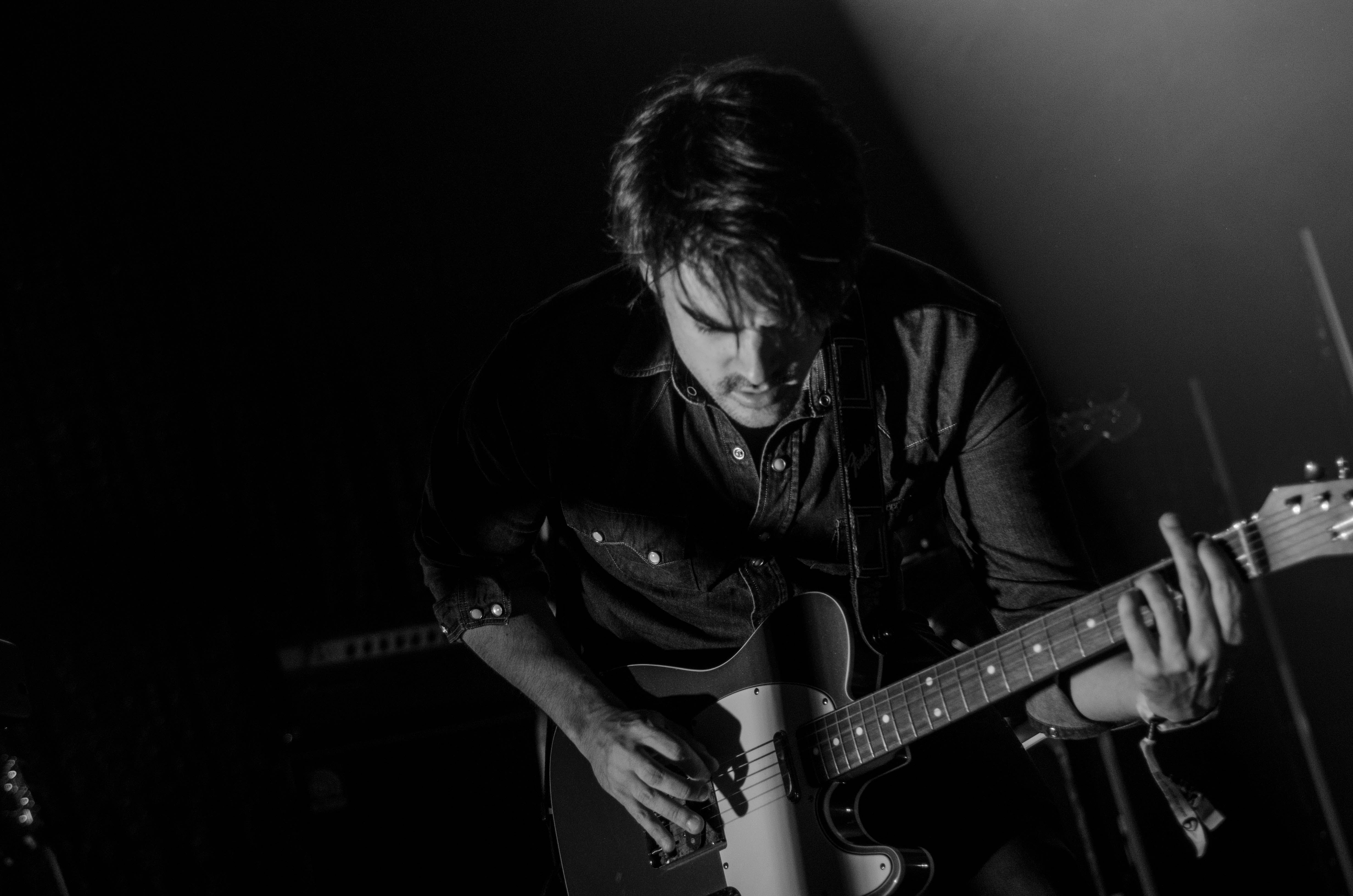 Grayscale Photo of Man Playing Electric Guitar