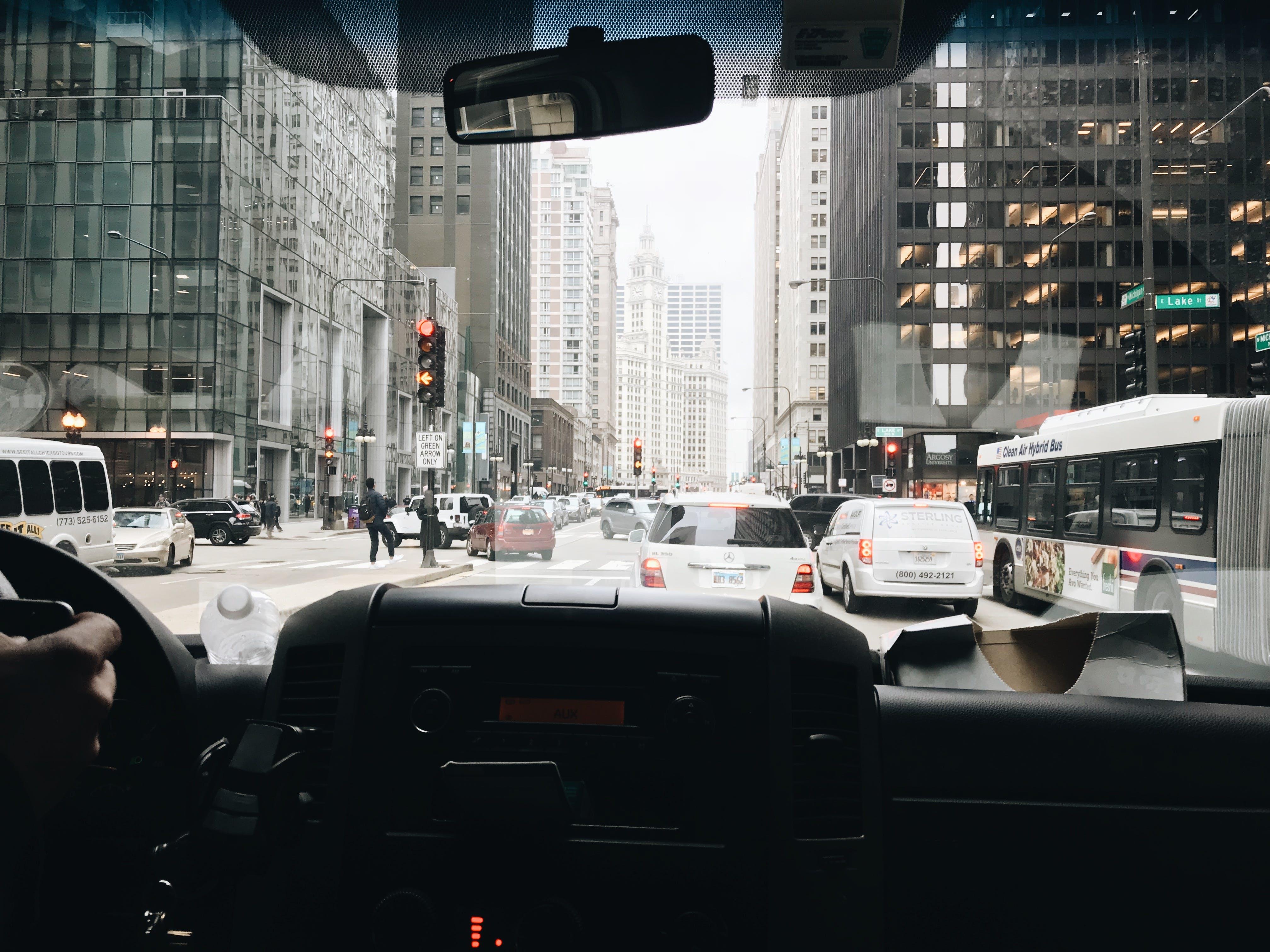 Vehicles Passing on Road in Between Buildings