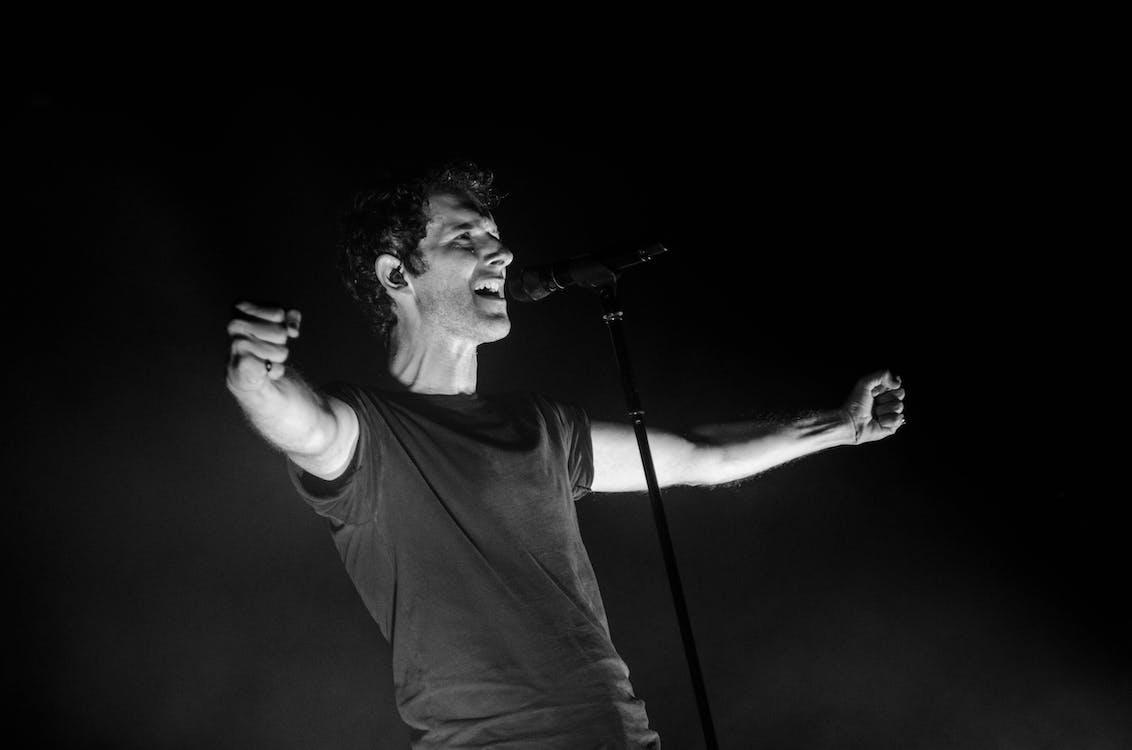 Greyscale Photo of Man Singing