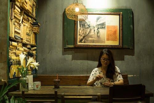 Kostenloses Stock Foto zu asiatische frau, blumen, brillen, drinnen