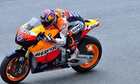 Man in Repsol Orange White and Blue Motorcycle Racing Gear Riding Sports Bike