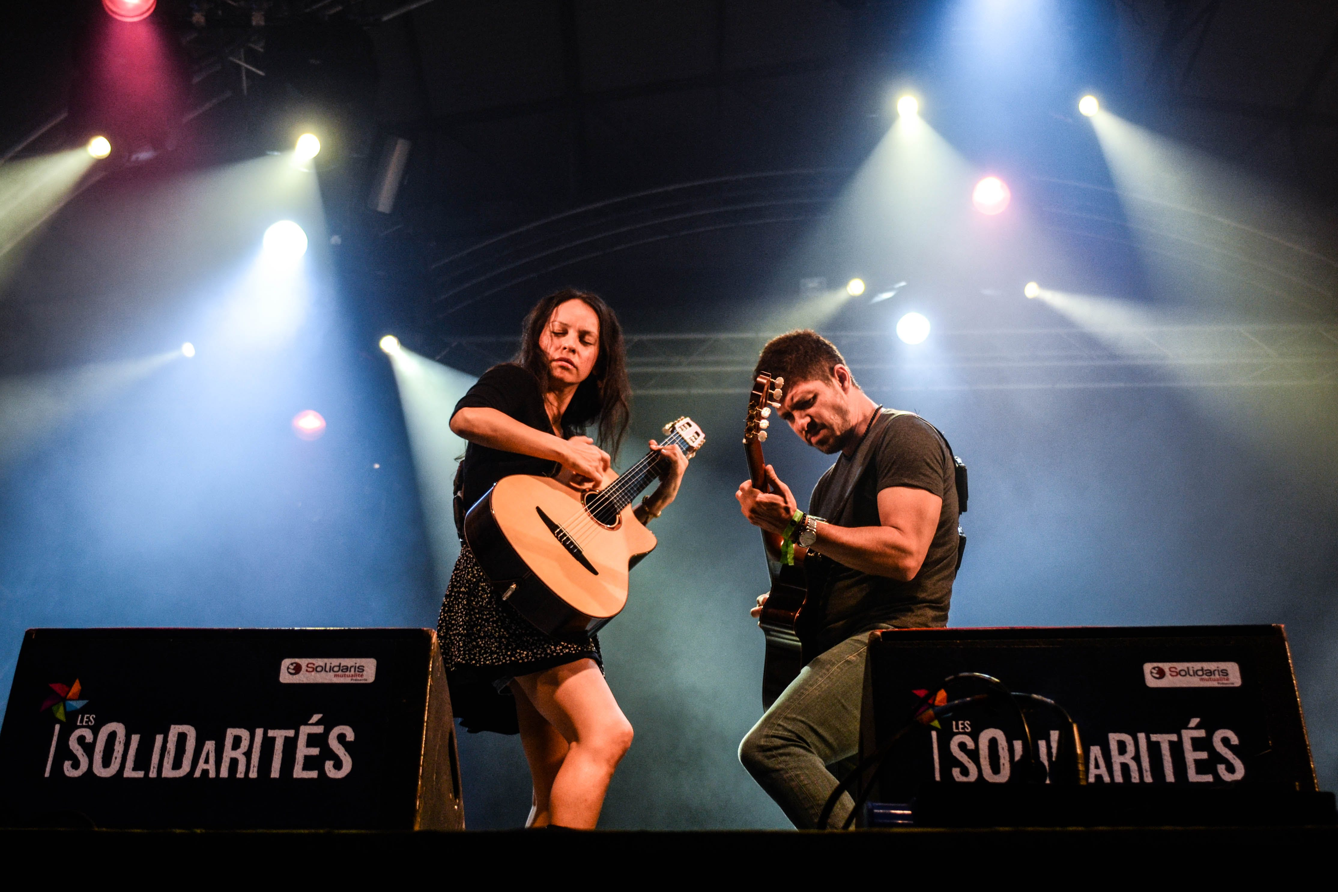 Man and Woman Playing Guitar on Stage at Solidarites