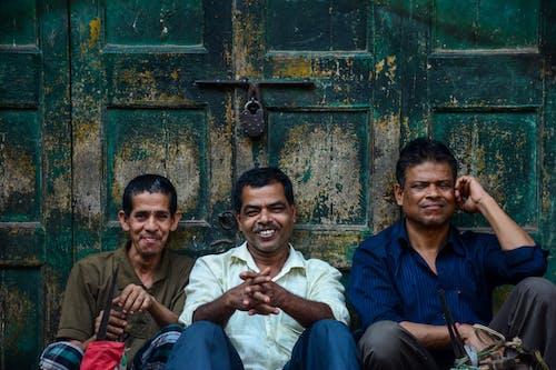 Three Men Smiling While Sitting Against Door