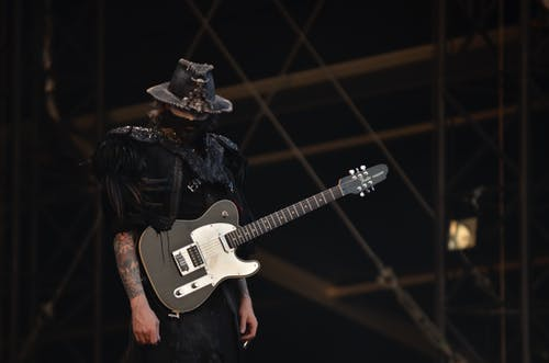Person in Black Shirt With a Black Telecaster Guitar