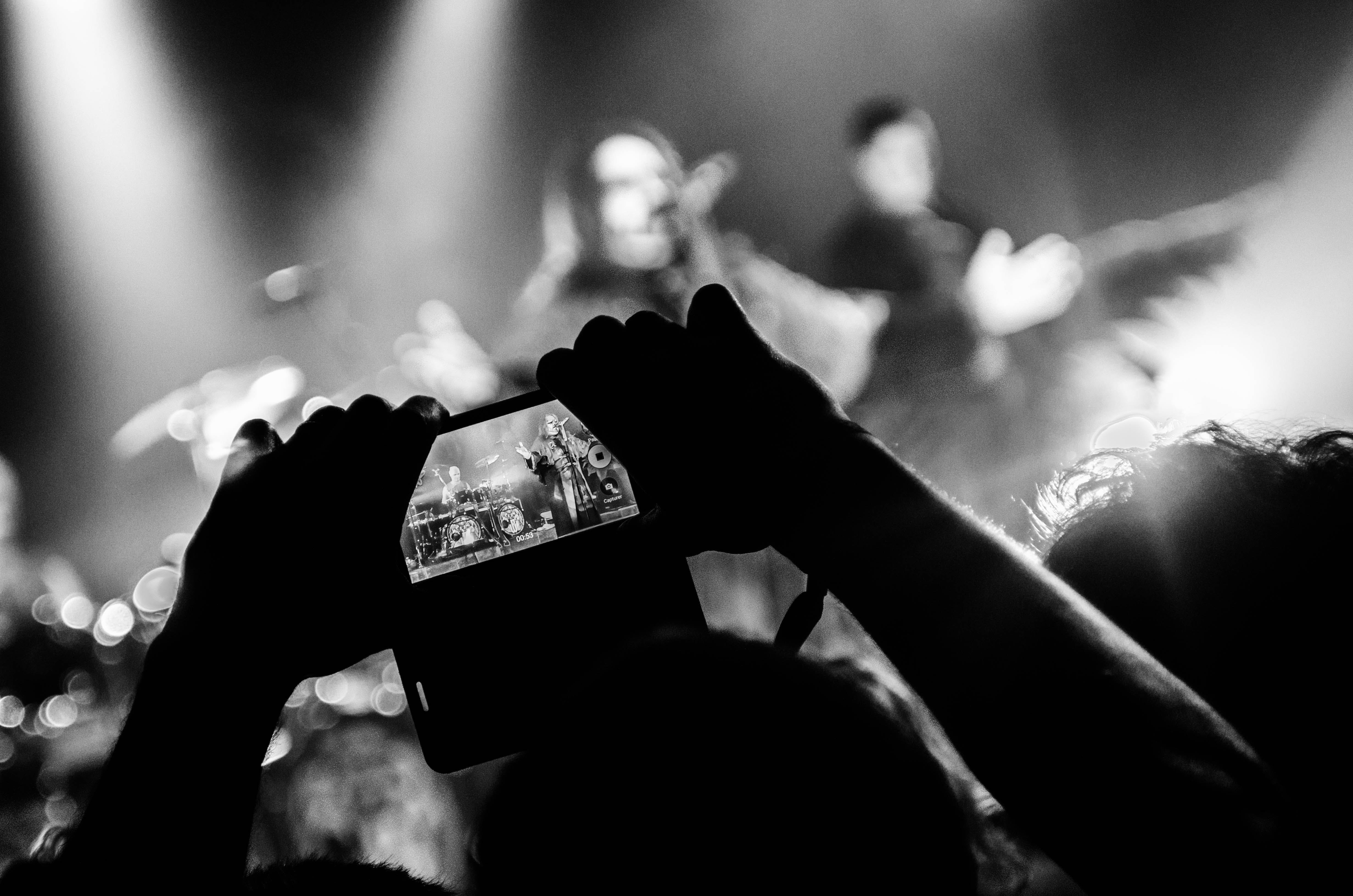 Grayscale Photography of Person Taking Picture of Band