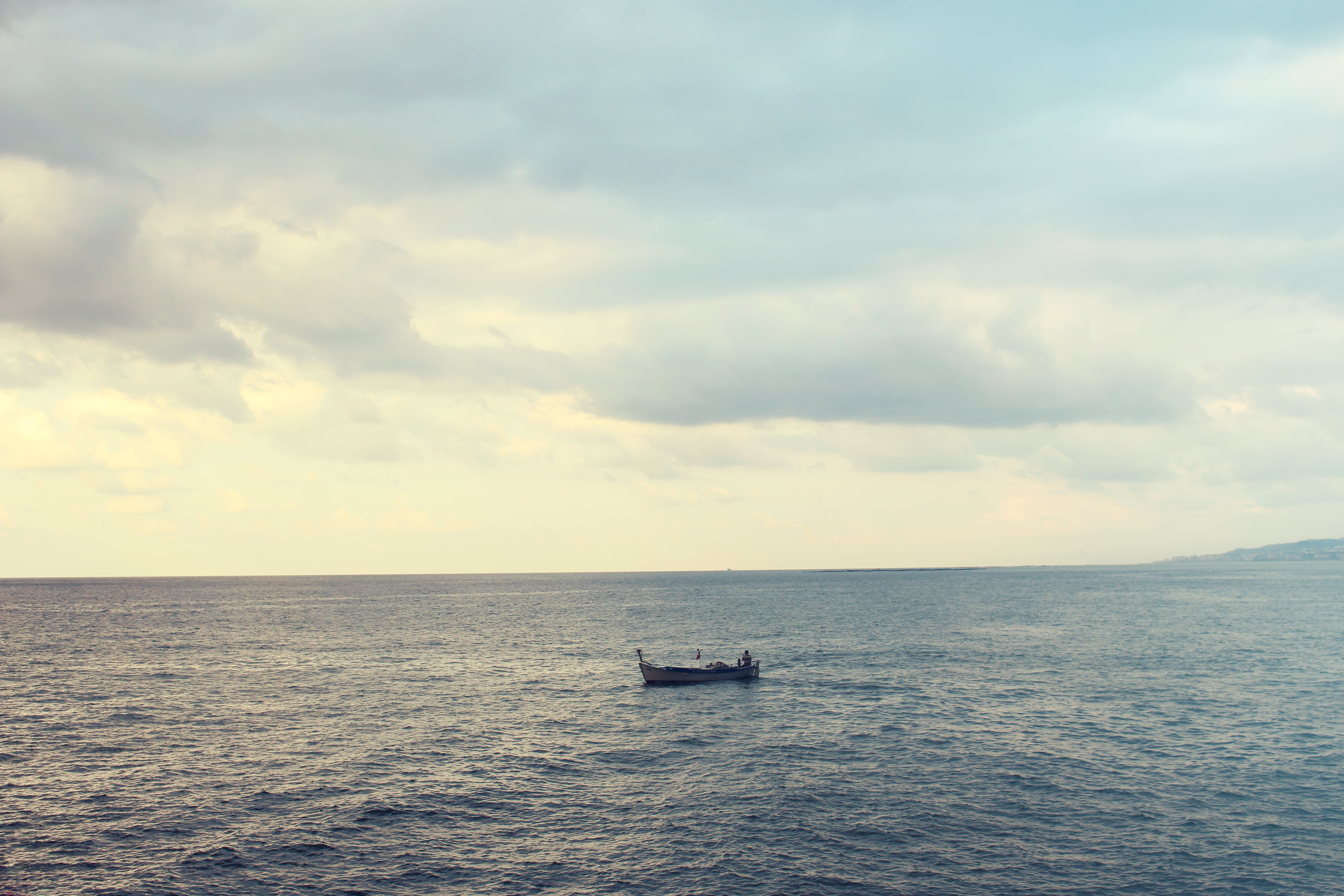 Wooden Boat on Water on Calm Body of Water during Cloudy Daytime Sky