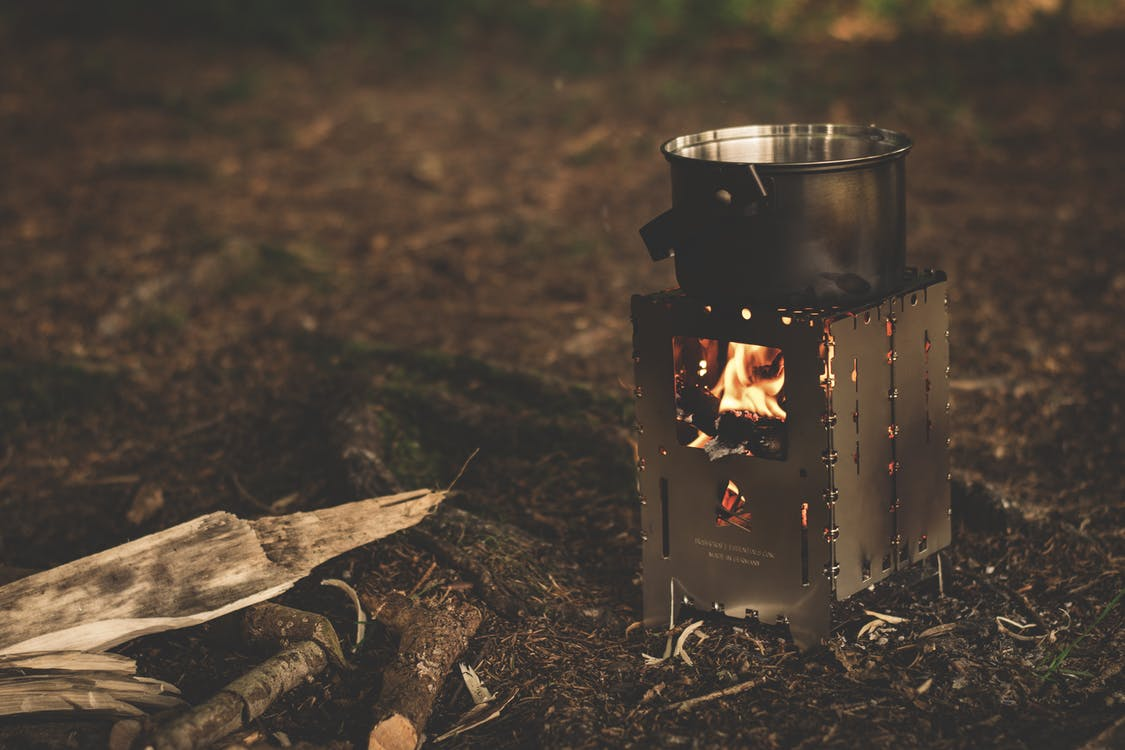 Stainless Steel Pot on Brown Wood Stove Outside during Night Time