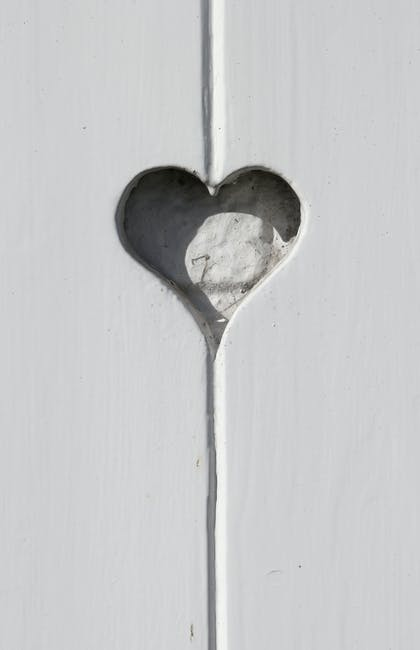 White wooden door with heart shape while looking the stars