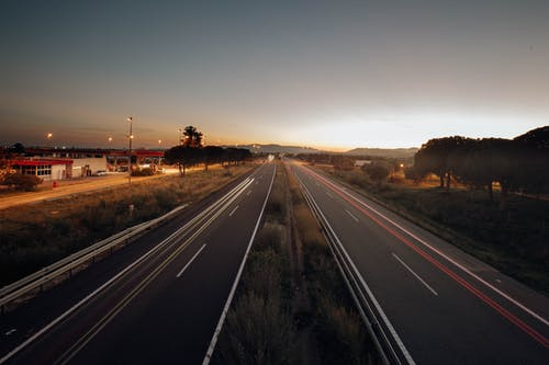 Fotos de stock gratuitas de anochecer, arboles, asfalto, autopista