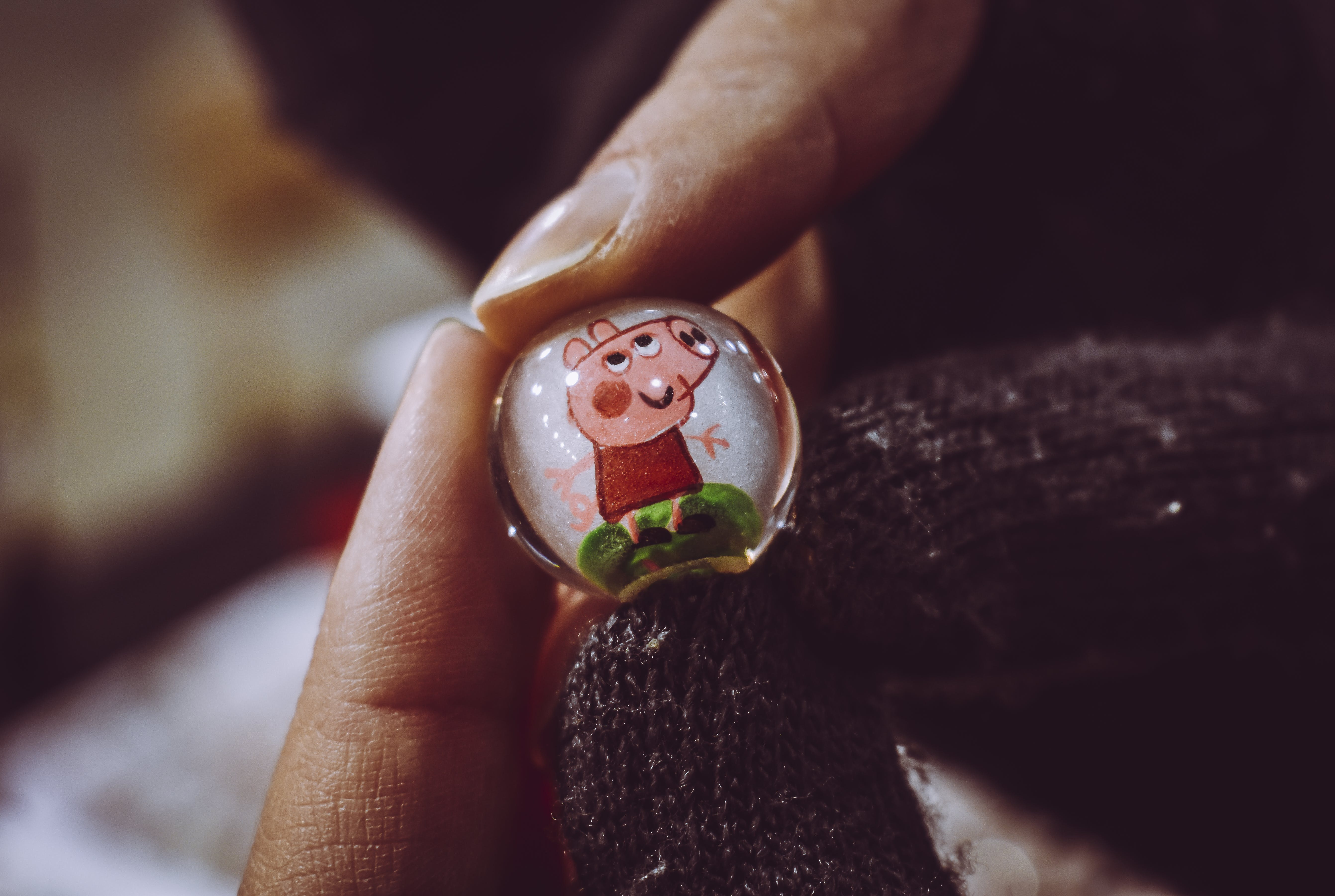 Person Holding Peppa Pig Toy Marble