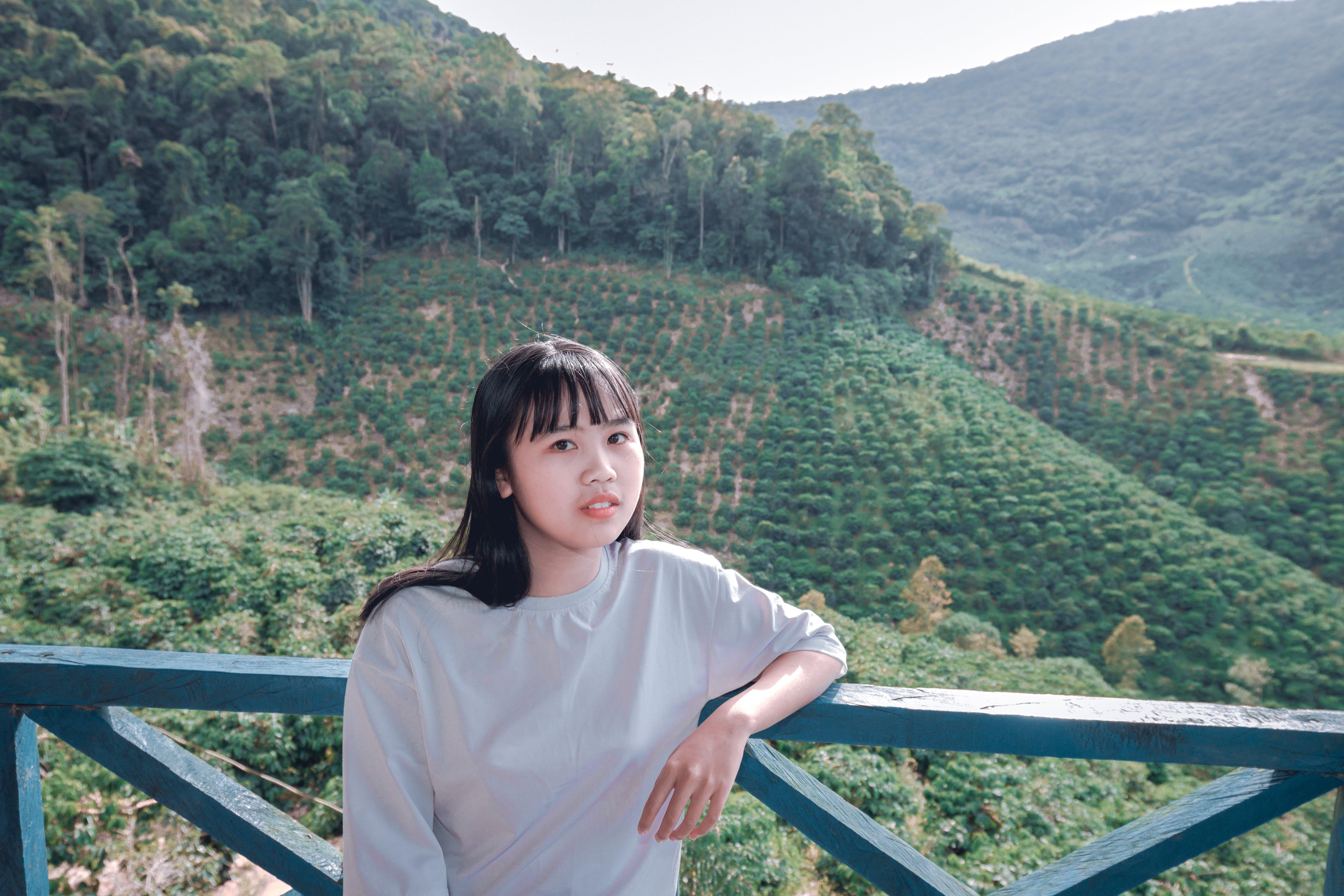 Woman Standing Near Green Mountain