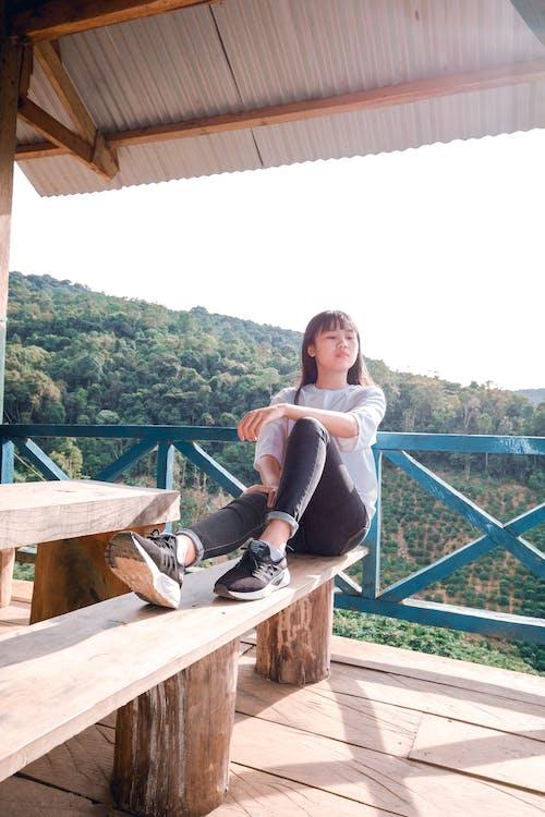 Foto d'estoc gratuïta de asiàtica, assegut, banc de fusta, dona