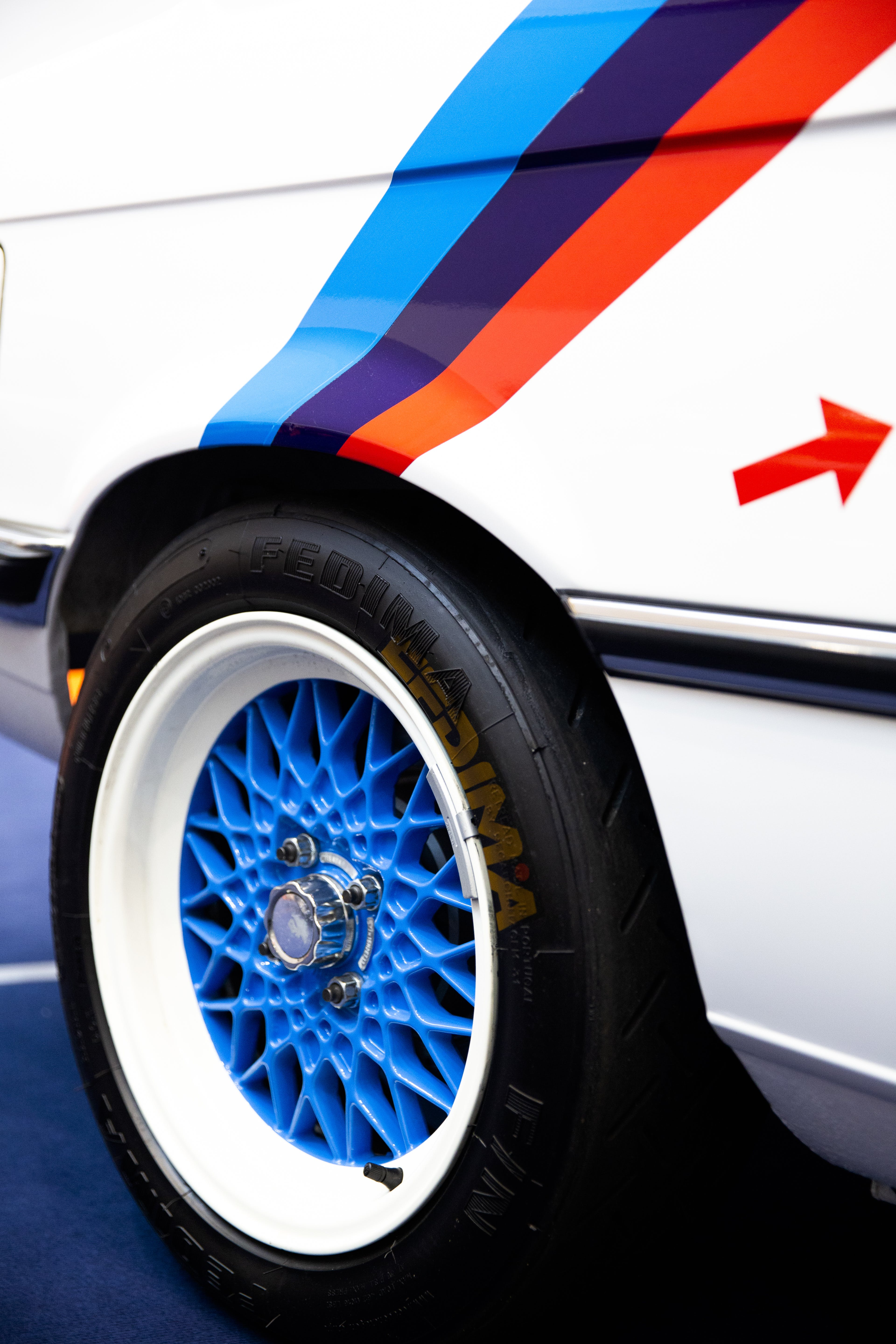 White Vehicle With Blue Multispoke Wheel and Tire