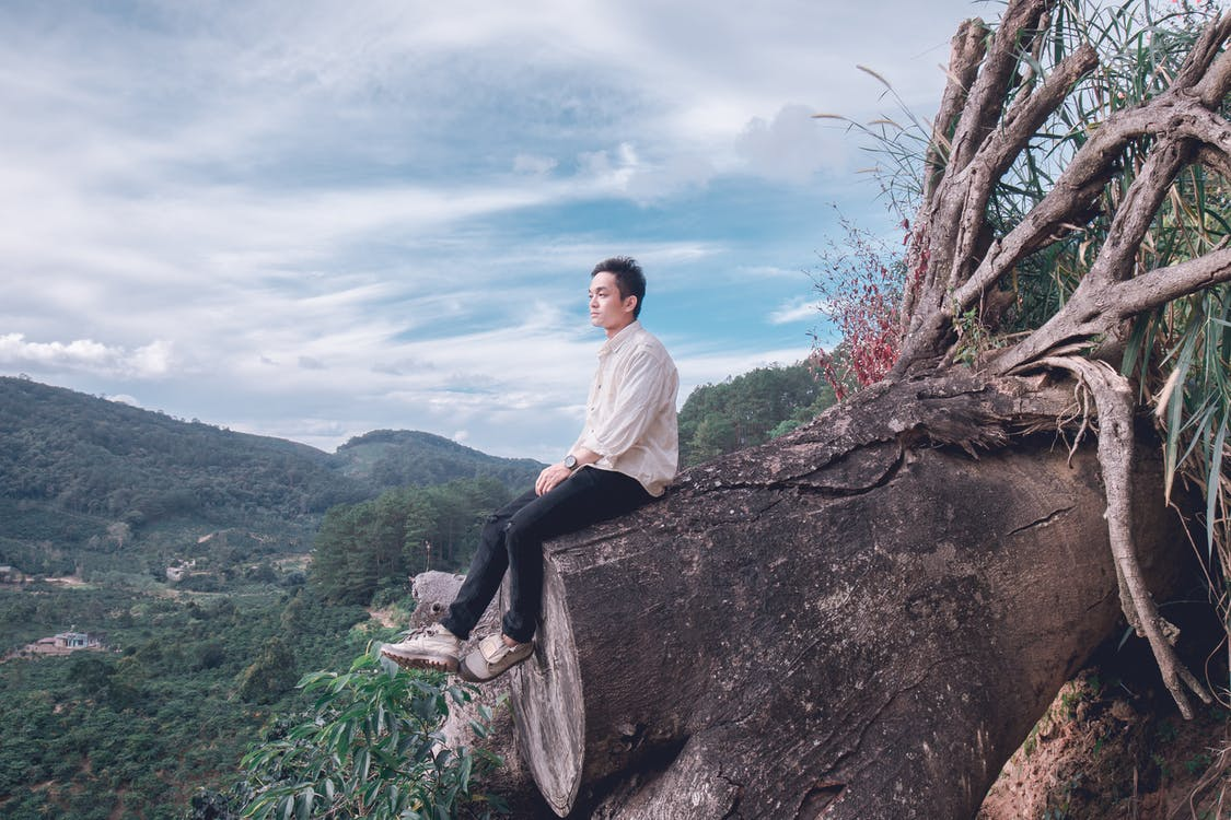 Man Sitting on Tree Trunk