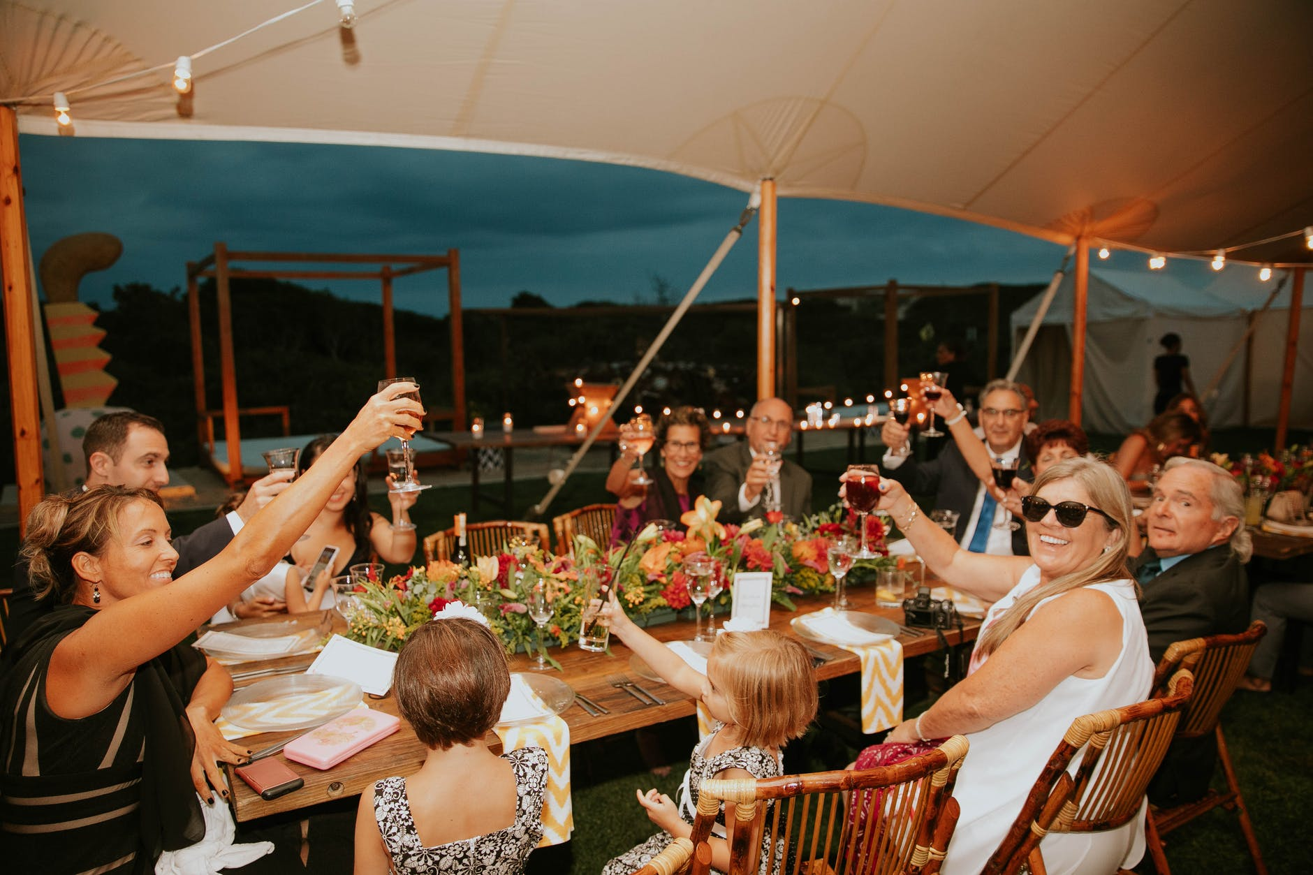 group of people raising their glasses to toast