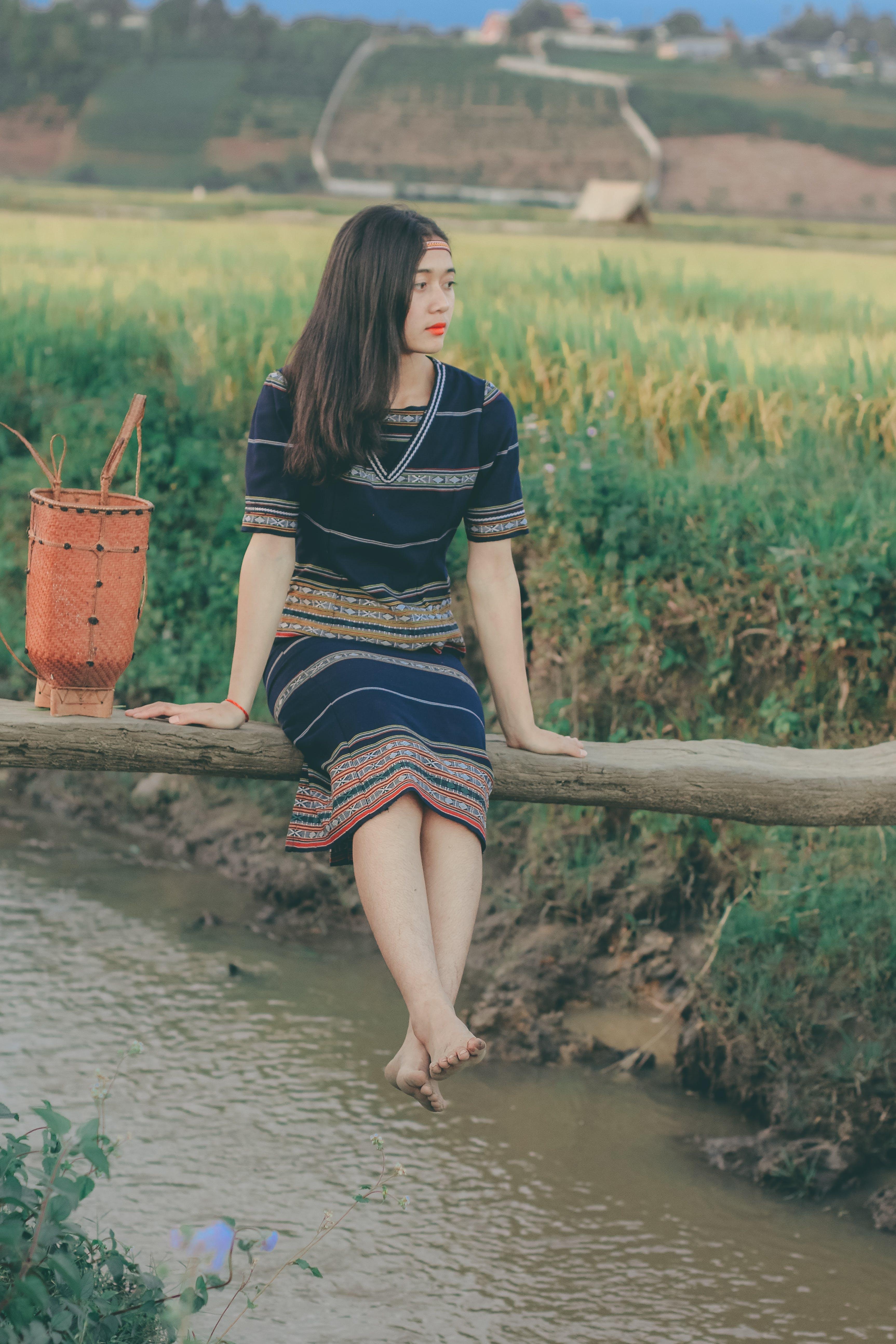 Woman Sitting on Bridge over Flowing Water