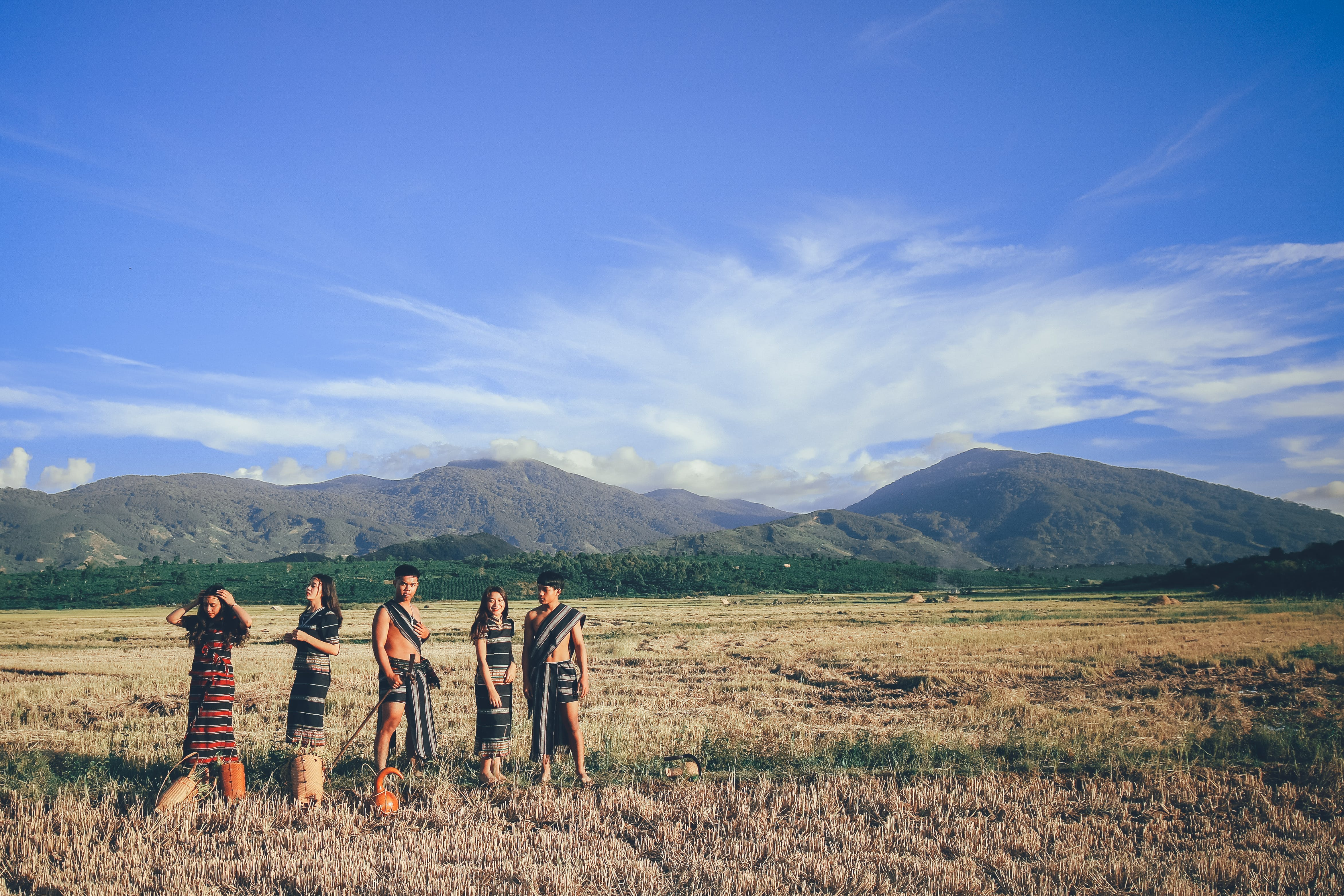 Five People Wearing Native Apparel Standing on Brown Grassfield Under Blue and White Cloudy Sky