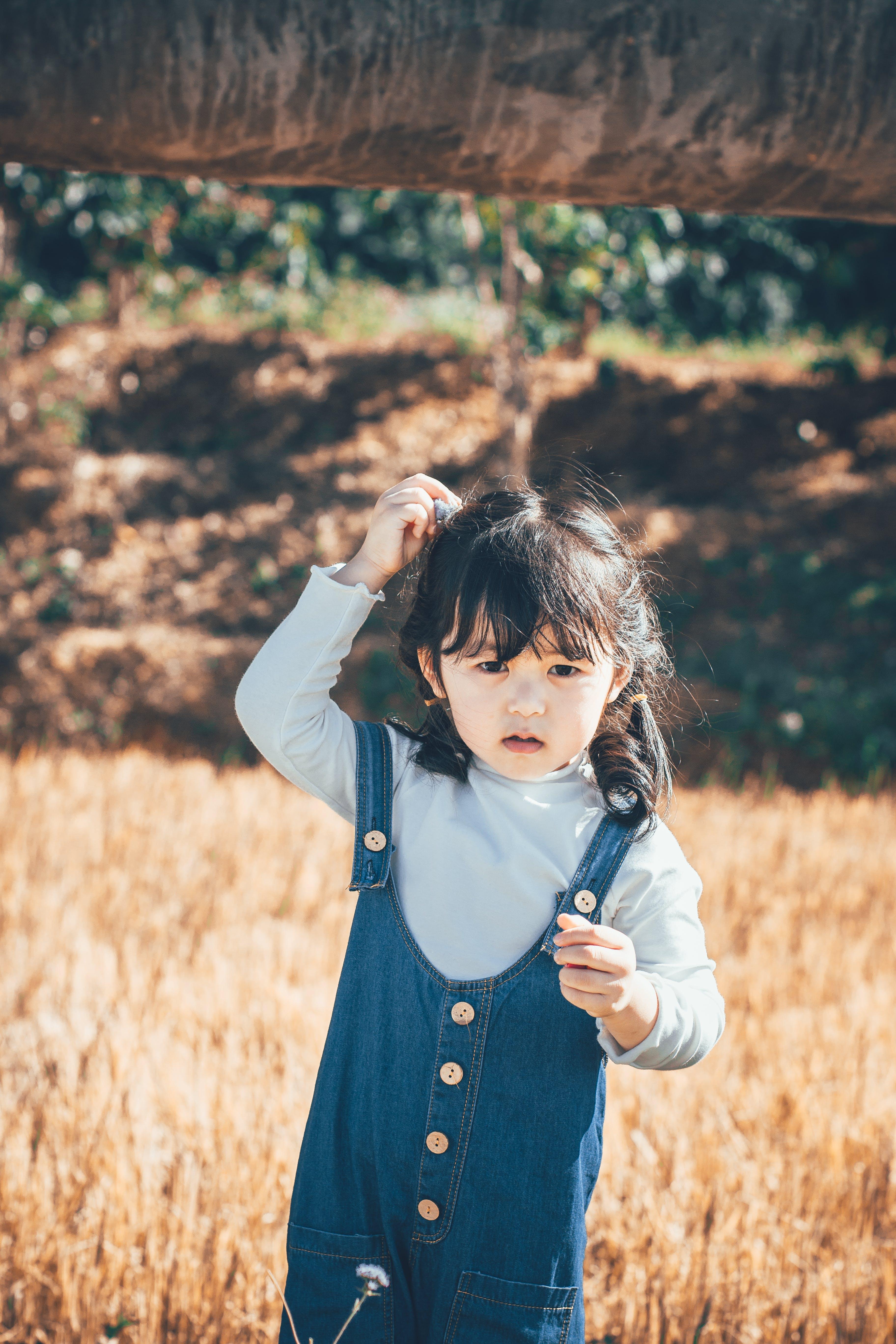 Kostenloses Stock Foto zu asiatisches kind, feld, freude, gras
