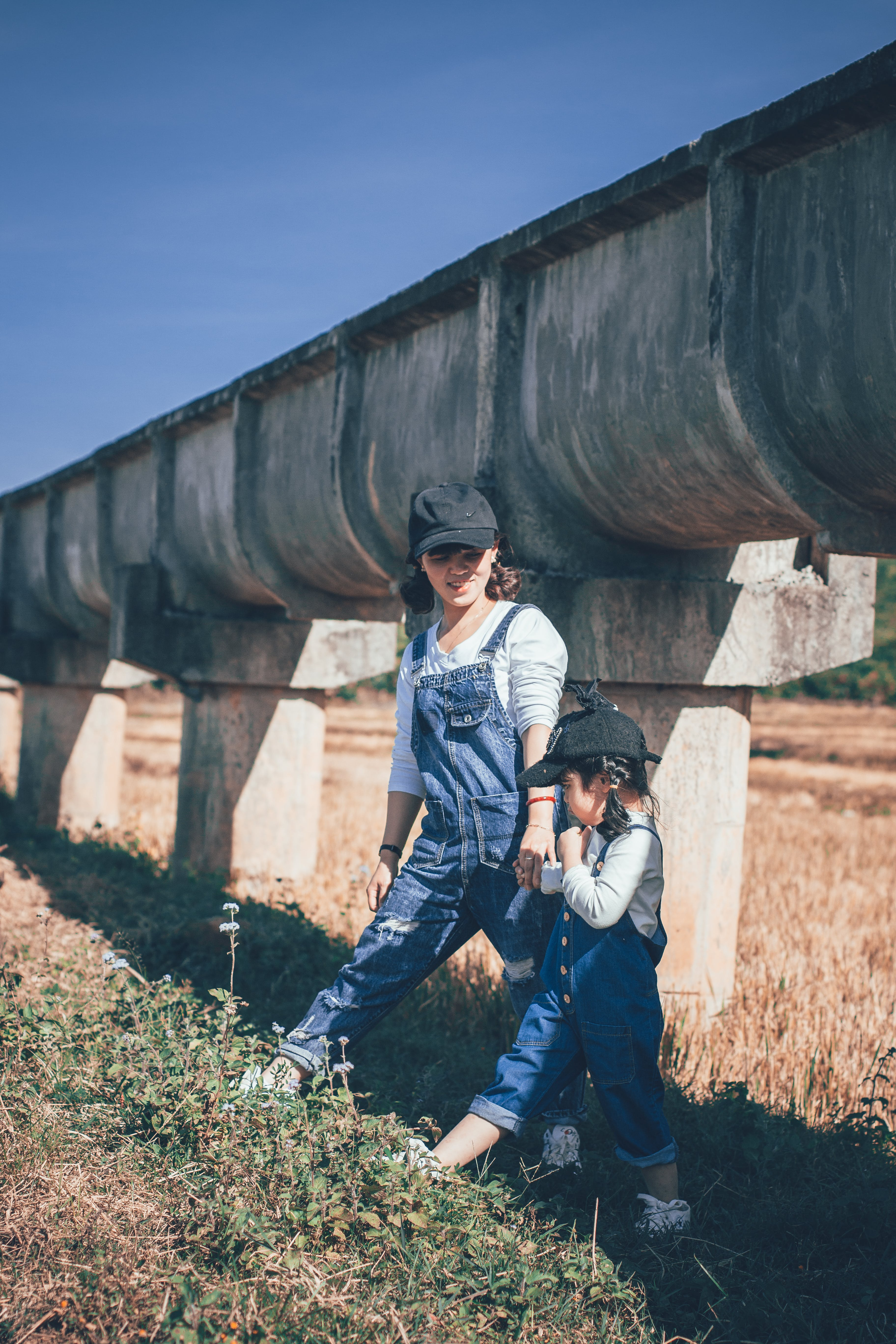 Woman and Girl Standing Under Large Sewage