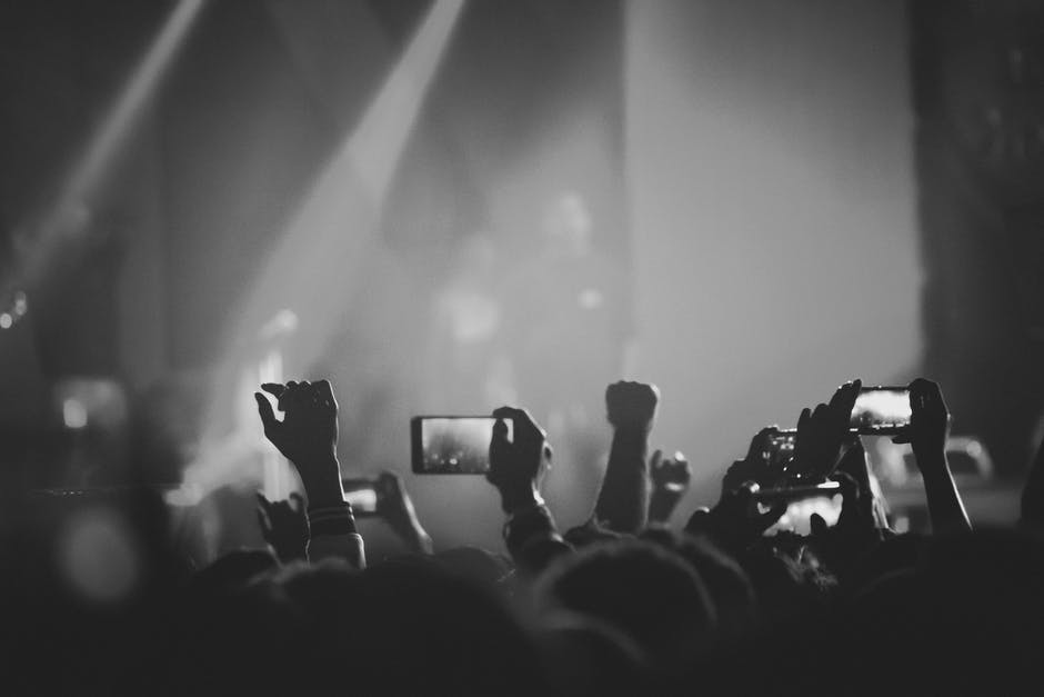 Grayscale photography of people holding smartphones while taking videos