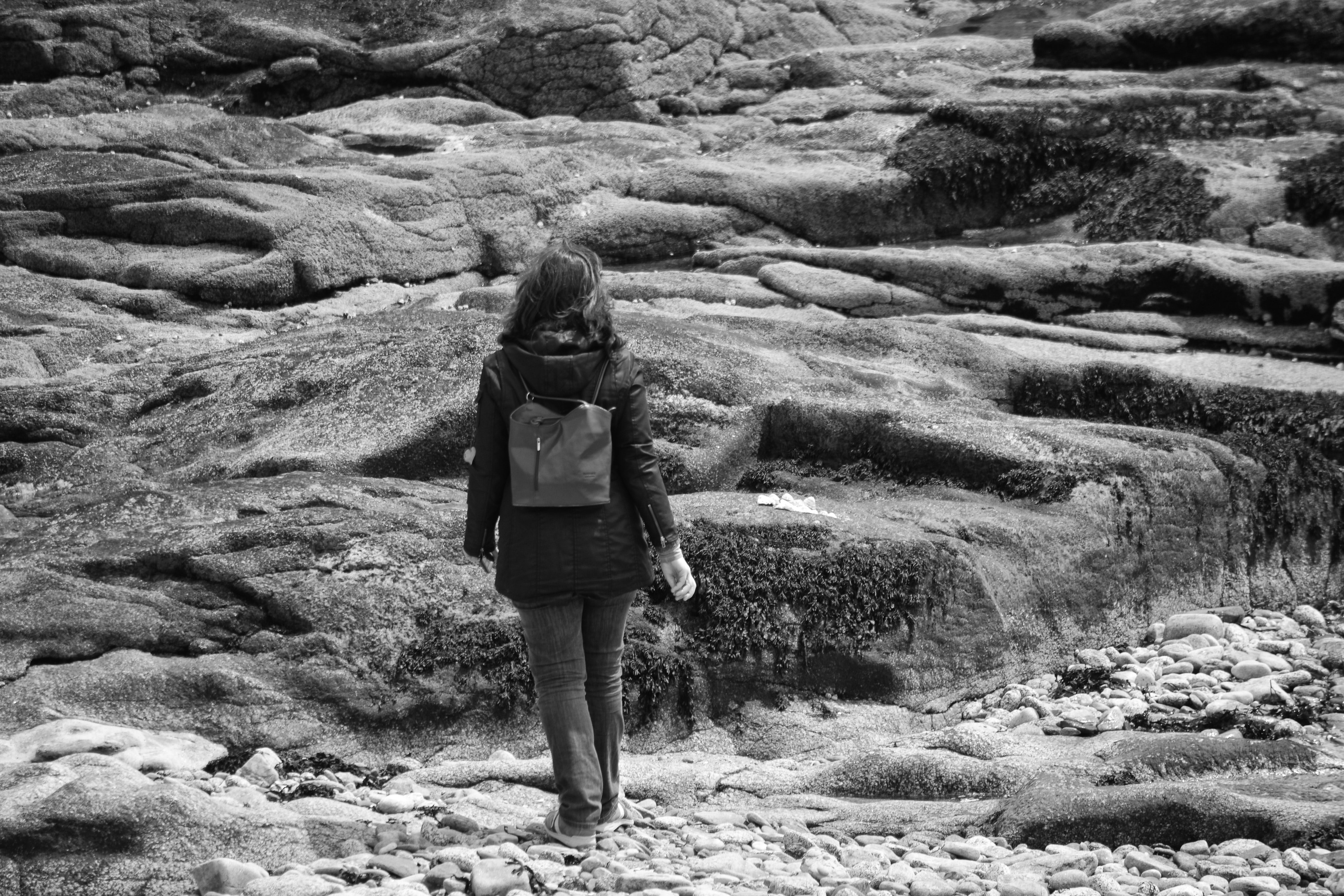 Gray Scale Woman in Black Hoodie Jacket on Concrete Rock