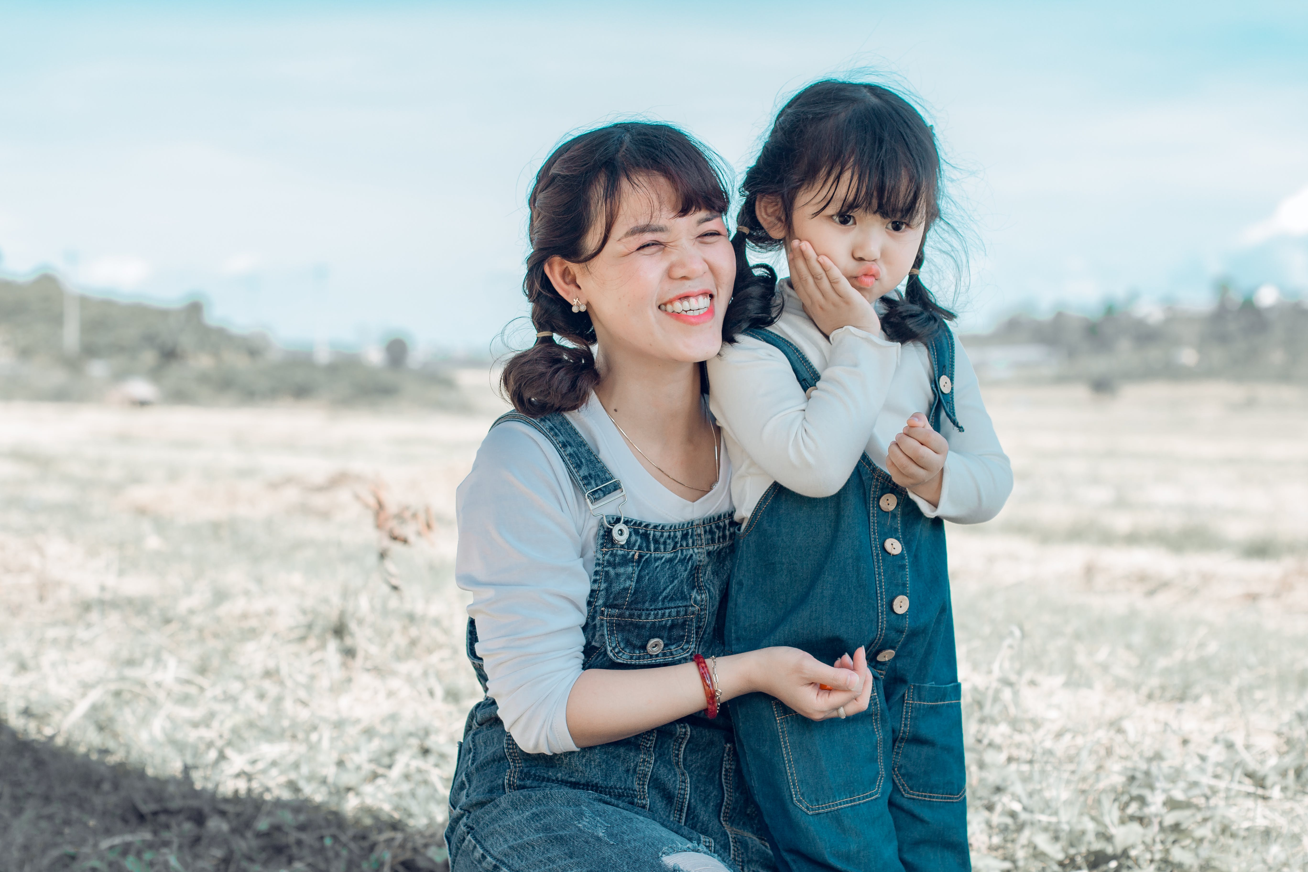 Woman Hugging Girl While Sitting on Grass Field
