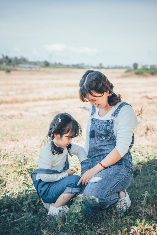 Smiling Woman and Girl Sitting on Grass Field
