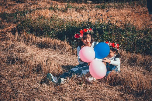 Woman Holding Pink and Blue Balloons