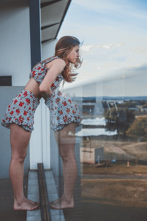 Photo of Woman Leaning Against Glass Balcony