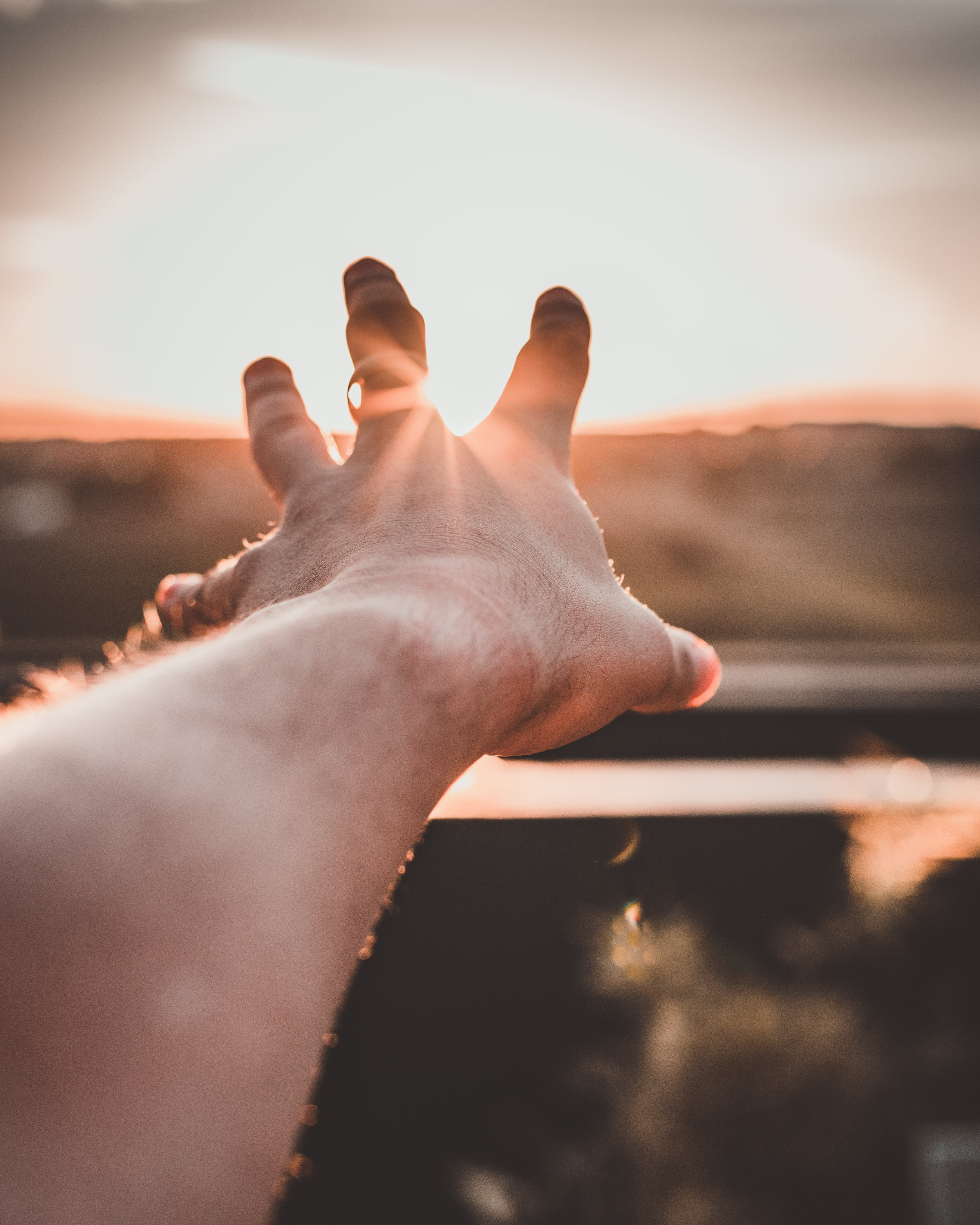 Close-Up Photo of Hand During Sunset