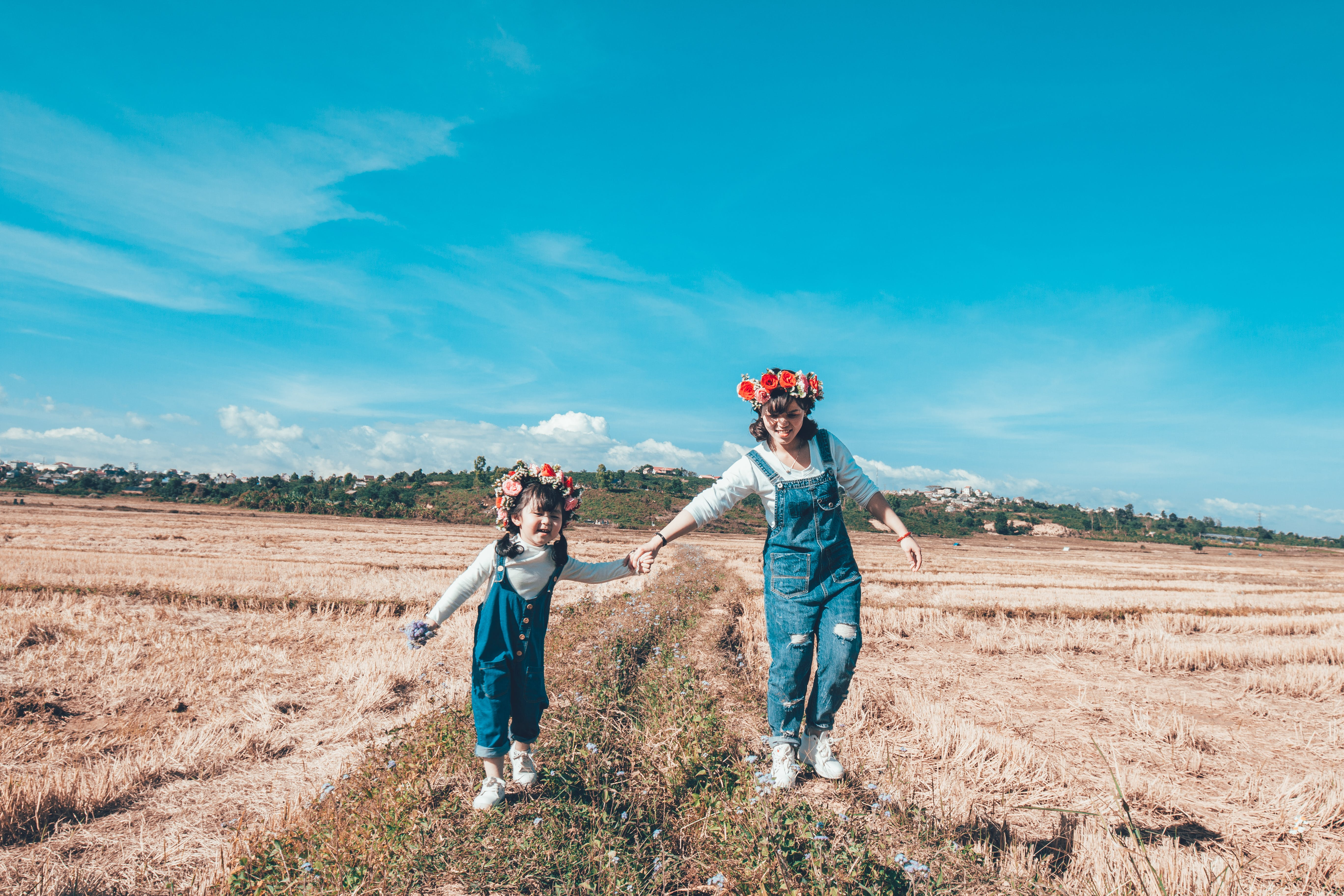 Woman and Girl Doing Hand in Hand Whole Walking on Grass Field