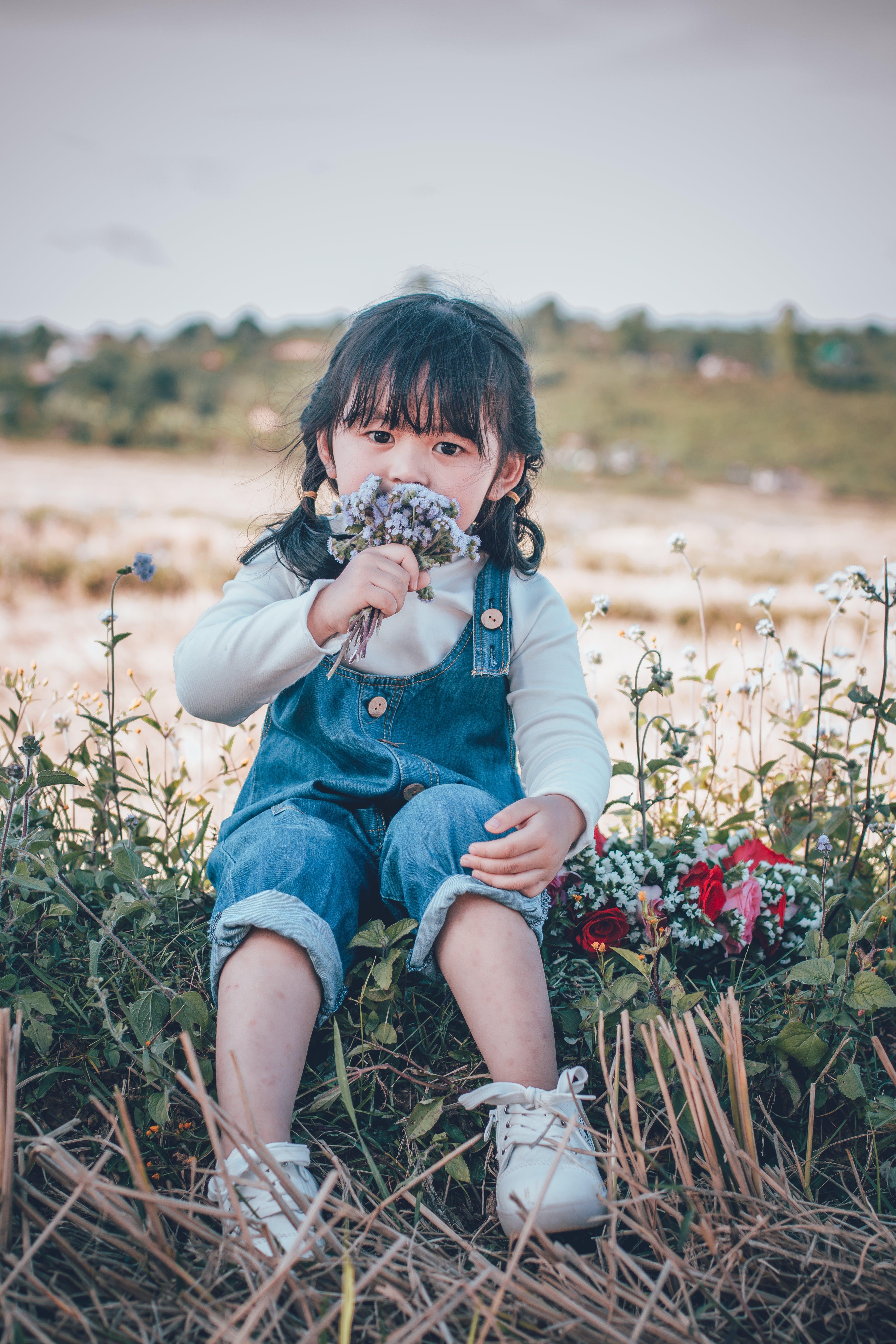 Kostenloses Stock Foto zu asiatisches kind, blumen, feld, gras