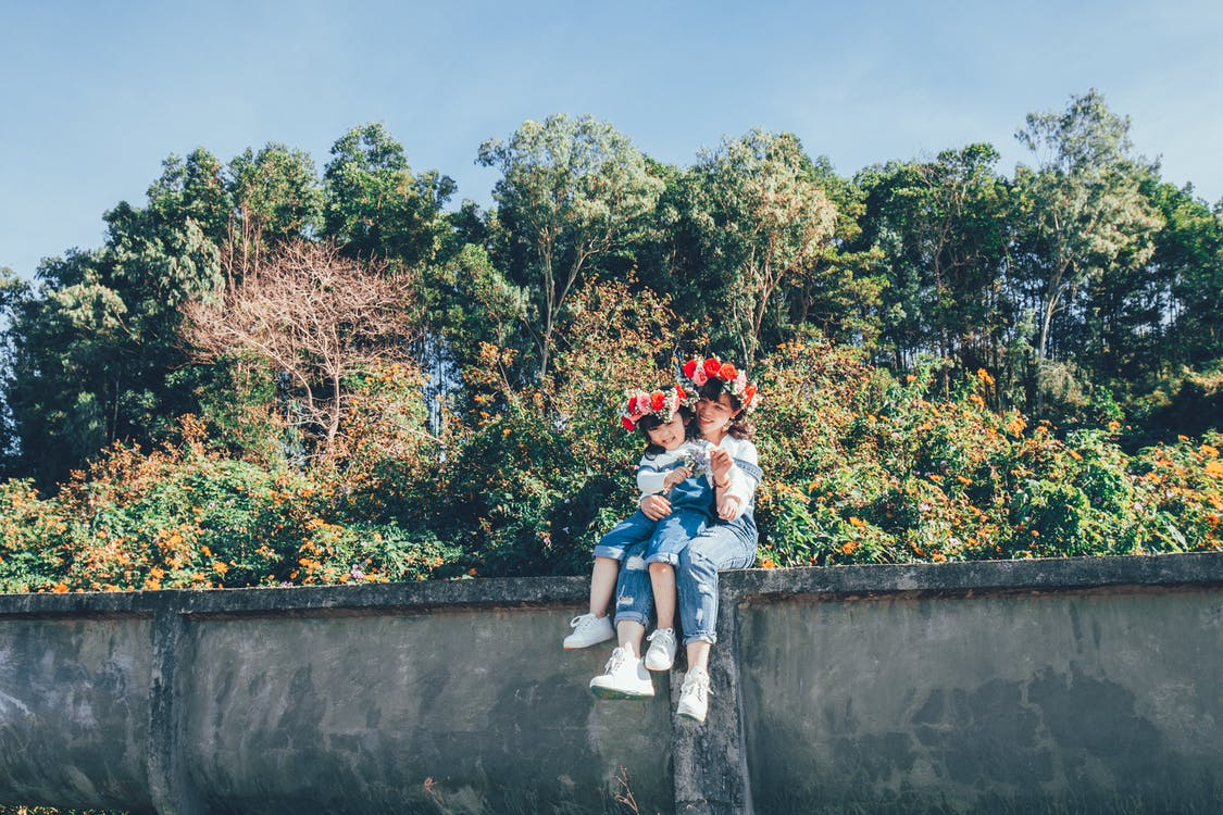 Woman and Girl Sitting on Concrete Wall
