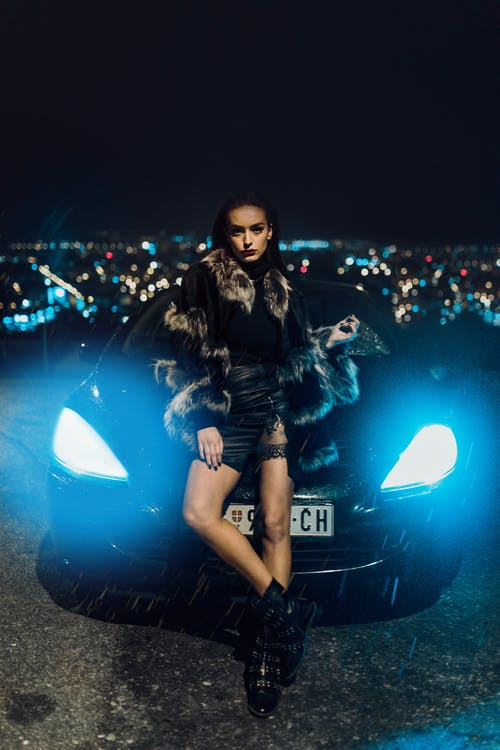 Woman Wearing Fur Jacket Leaning on Car's Hood