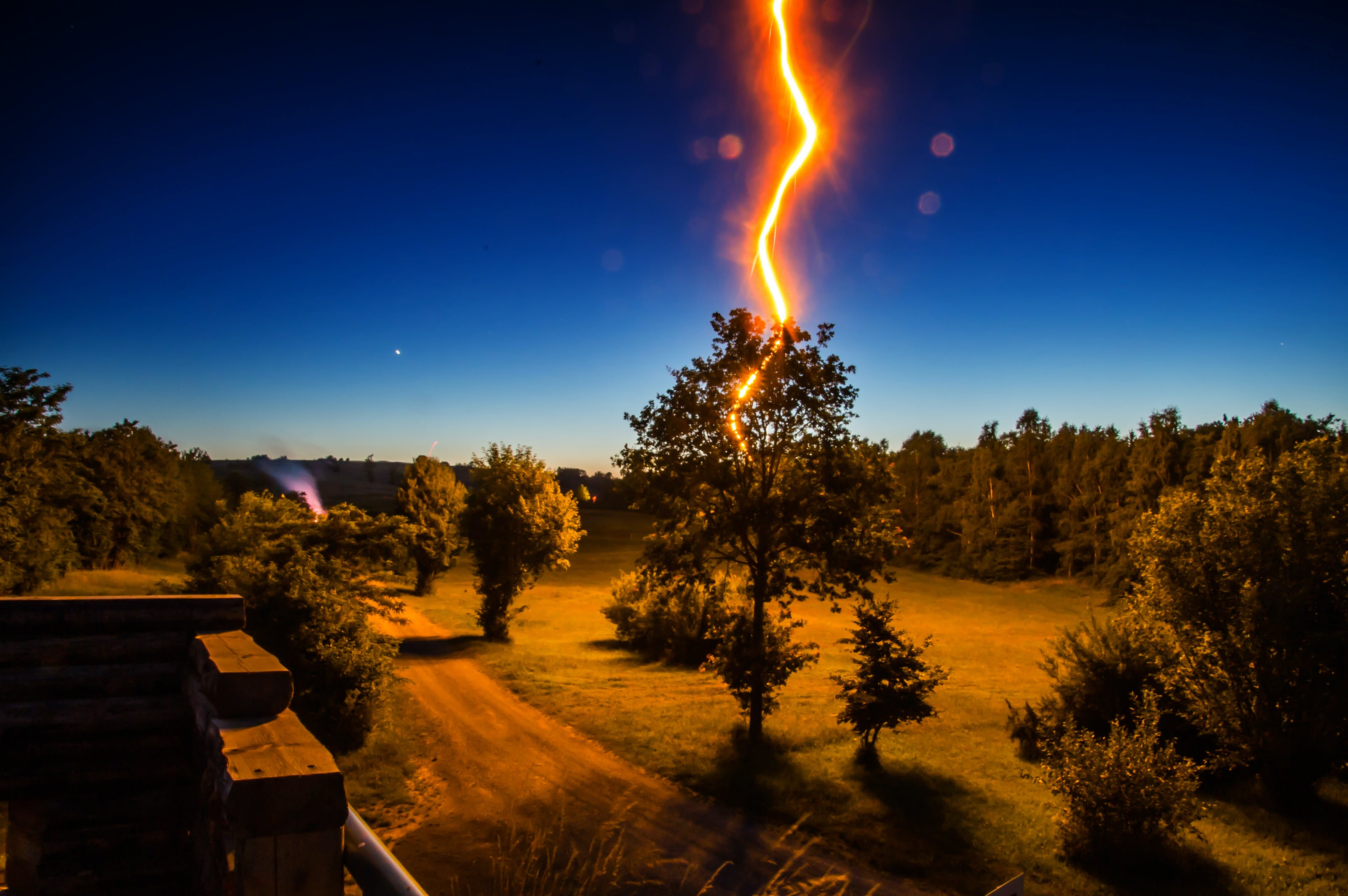 Lightning Strikes Tree in Front of House during Nighttime