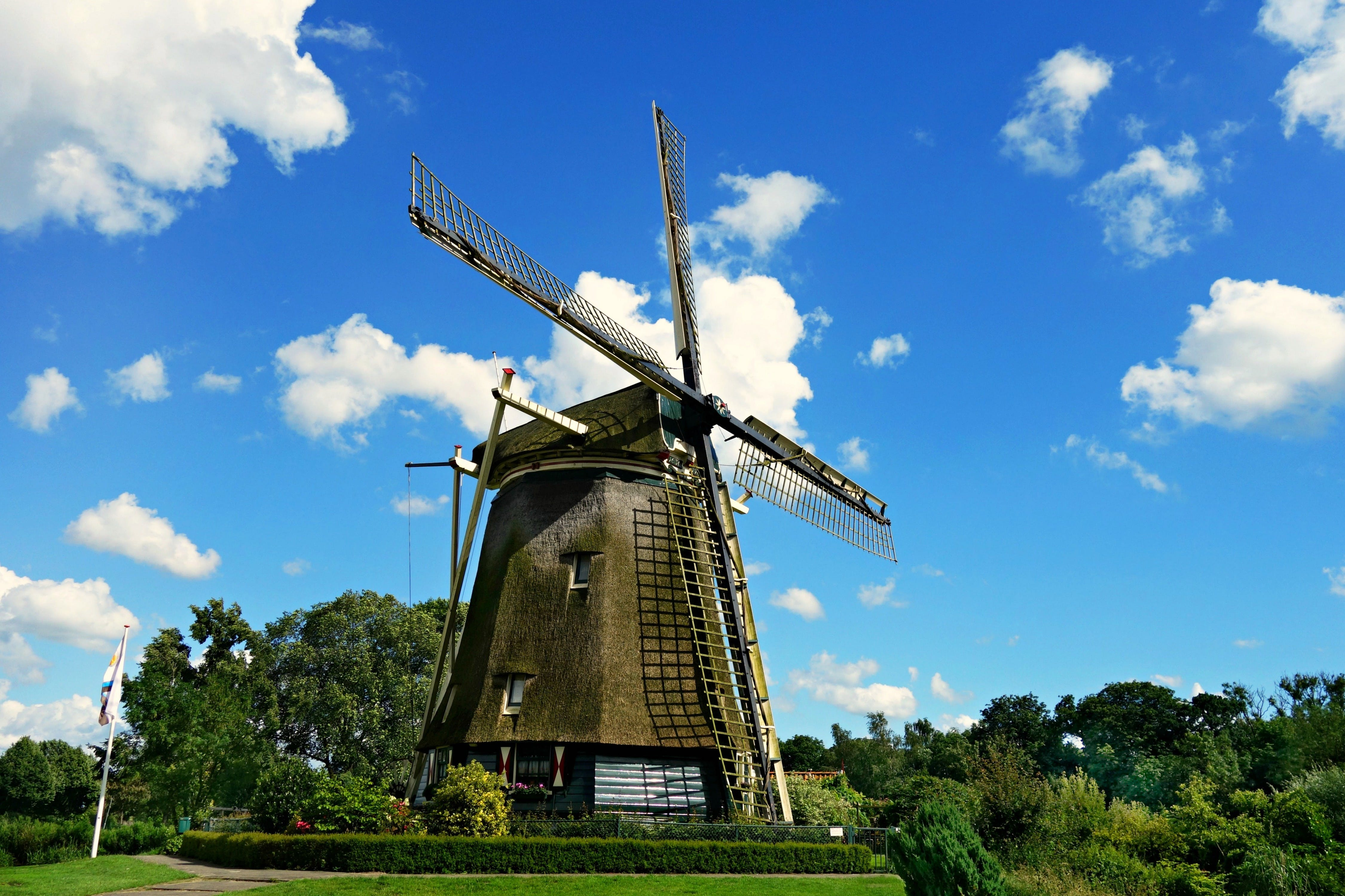 Brown and Black Windmill Under Cumulus Clouds Surrounded by Green Leaf Trees
